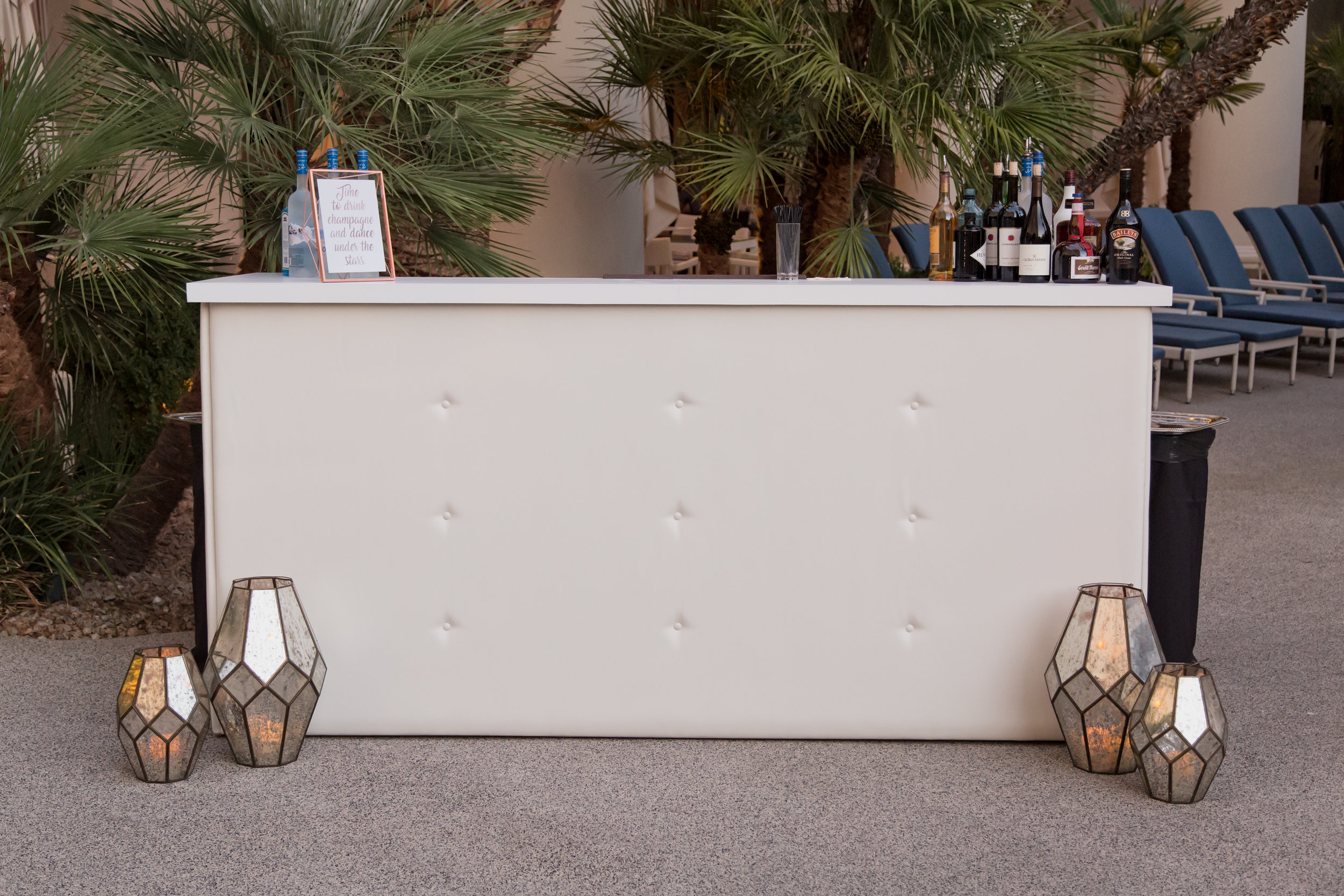 White tufted bar surround.Destination Wedding Planner  Andrea Eppolito ·Photos by  Adam Frazier Photography ·Floral and Decor by  Destinations by Design · Lighting by  LED Unplugged ·Venue · Invitations  Ceci New York  · Menus by  Alligator Soup