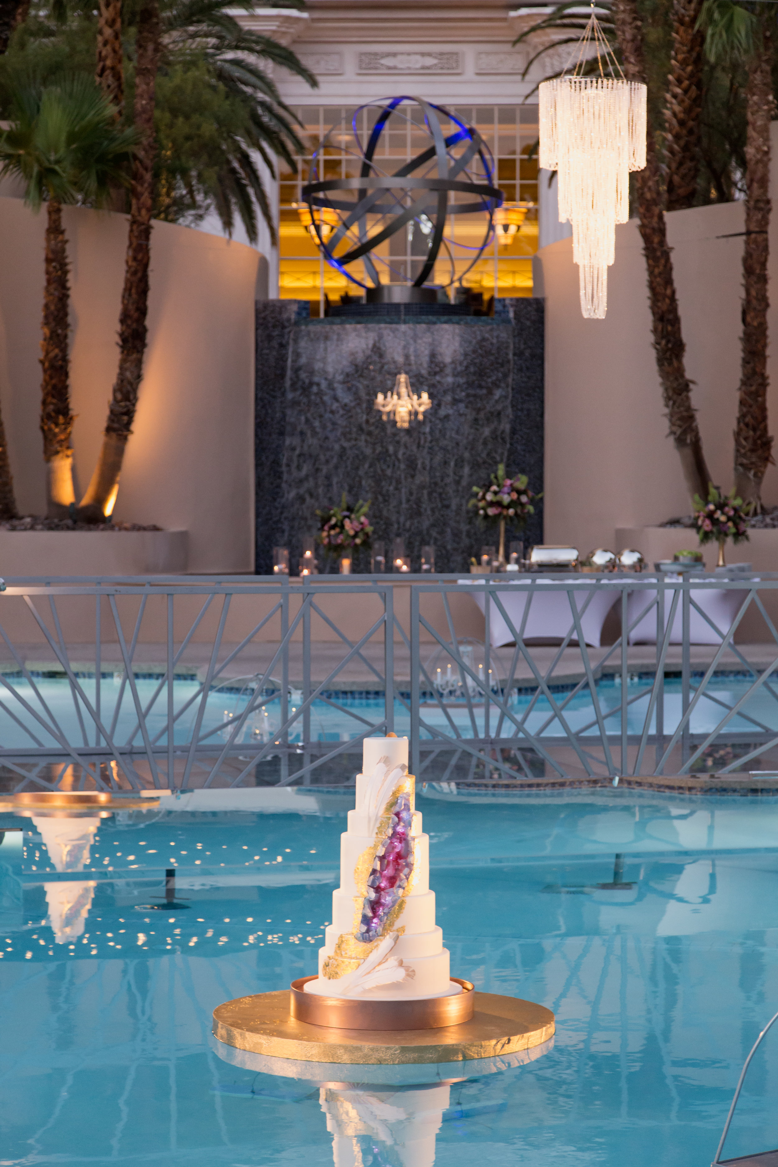 Floating wedding cake with geode design and chandeliers at poolside wedding in Las Vegas.Destination Wedding Planner  Andrea Eppolito ·Photos by  Adam Frazier Photography ·Floral and Decor by  Destinations by Design · Lighting by  LED Unplugged ·Venue · Invitations  Ceci New York  · Menus by  Alligator Soup