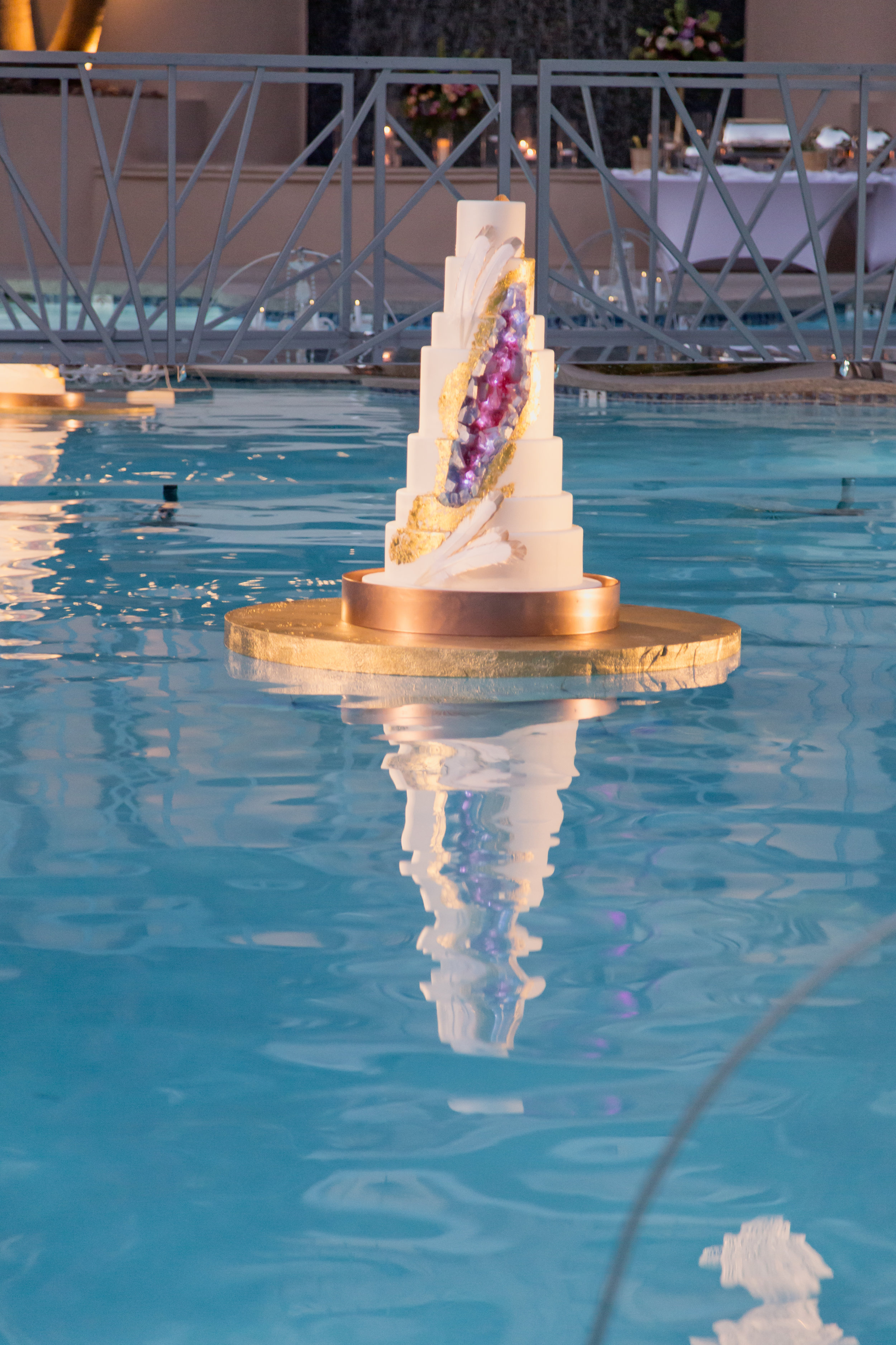 Geode wedding cake floating in pool at Four Seasons.Destination Wedding Planner  Andrea Eppolito ·Photos by  Adam Frazier Photography ·Floral and Decor by  Destinations by Design · Lighting by  LED Unplugged ·Venue · Invitations  Ceci New York  · Menus by  Alligator Soup