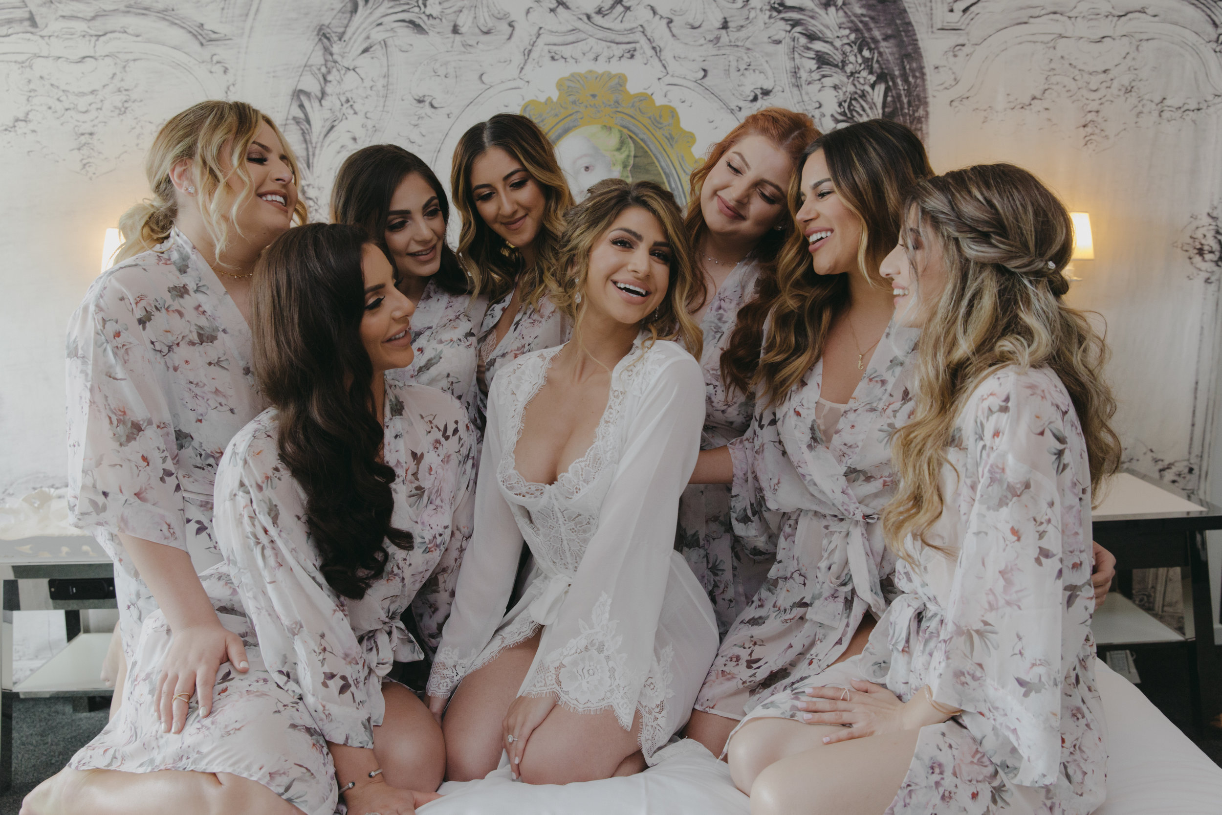 Bride surrounded by bridesmaids in robes.  Luxury Destination Wedding Planning and Event Design by  Andrea Eppolito Events  · Photos by  Stephen Salazar