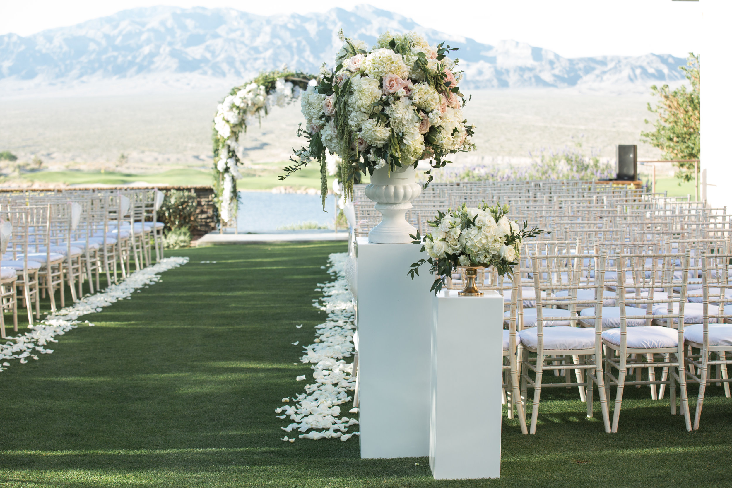 Romantic wedding ceremony on golf course. Luxury Destination Wedding Planning and Event Design by  Andrea Eppolito Events  · Photos by  Stephen Salazar  · Flowers by  Naakiti Floral  ·  Rentals by RSVP · Lighting by  LED Unplugged   · Venue  Paiute Golf Course .  Dress by  Berta  · Shoes by  Jimmy Choo