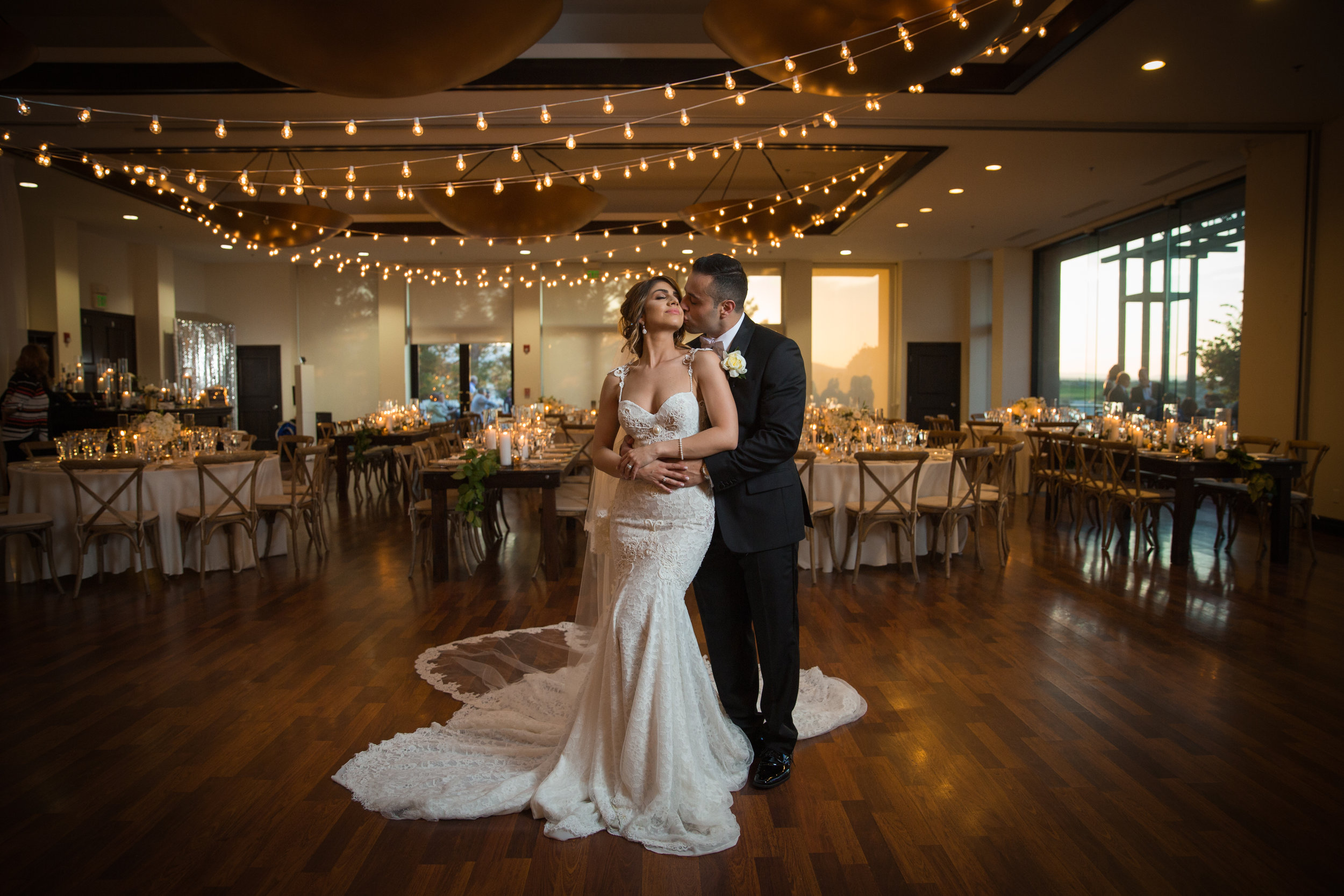 Bride and groom in rustic glam wedding reception with bistro lighting. Luxury Destination Wedding Planning and Event Design by  Andrea Eppolito Events  · Photos by  Stephen Salazar  · Flowers by  Naakiti Floral  ·  Rentals by RSVP · Lighting by  LED Unplugged   · Venue  Paiute Golf Course .  Dress by  Berta  · Shoes by  Jimmy Choo