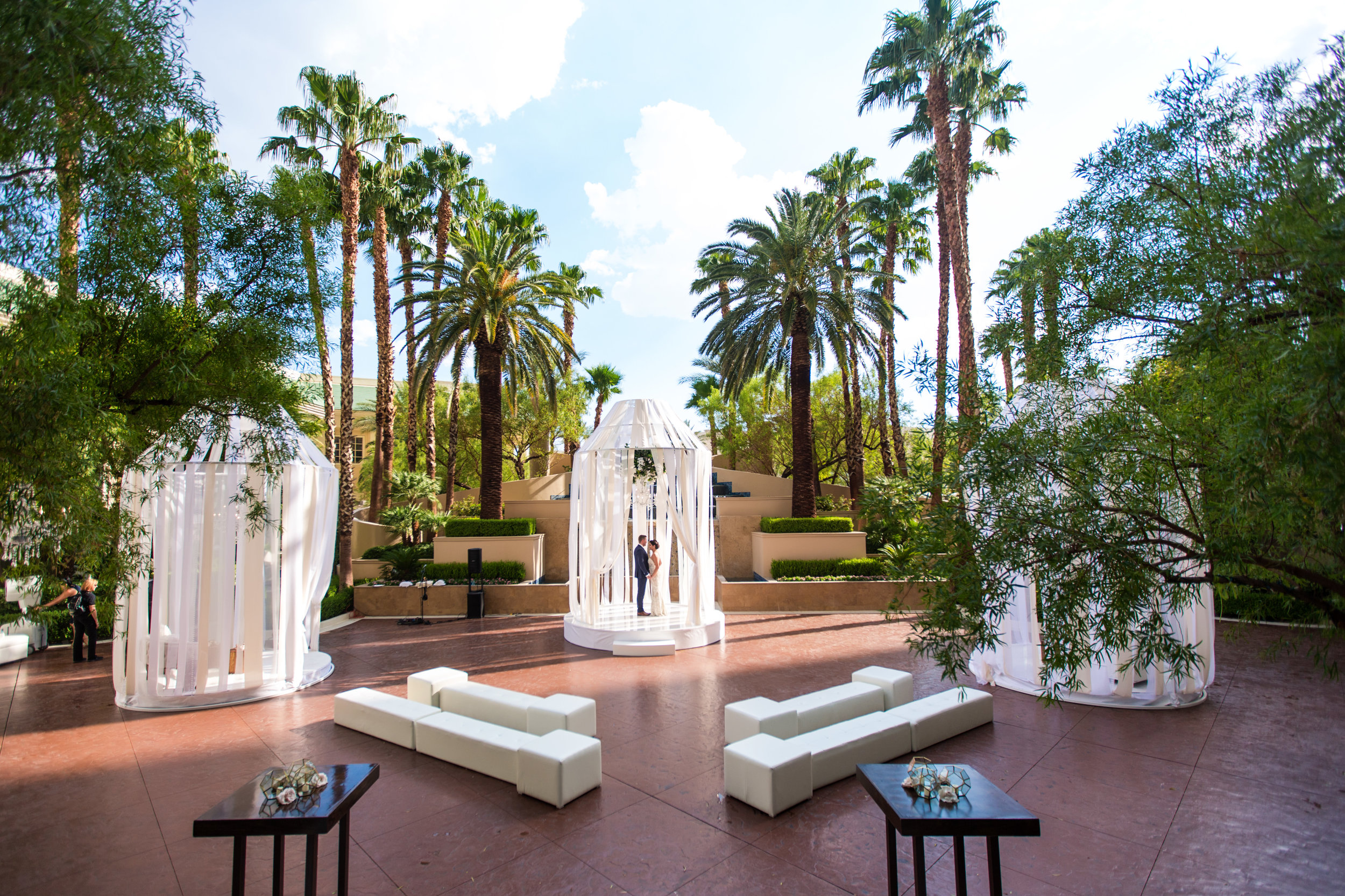 OUtdoor wedding ceremony with oversized bird cages.Wedding Planning by  Andrea Eppolito Events  · Photography by  Shandro Photo   · Wedding Venue  Four Seasons Las Vegas  · Floral and Decor by  Destination by Design  · Chandeliers and Lighting by  LED Unplugged