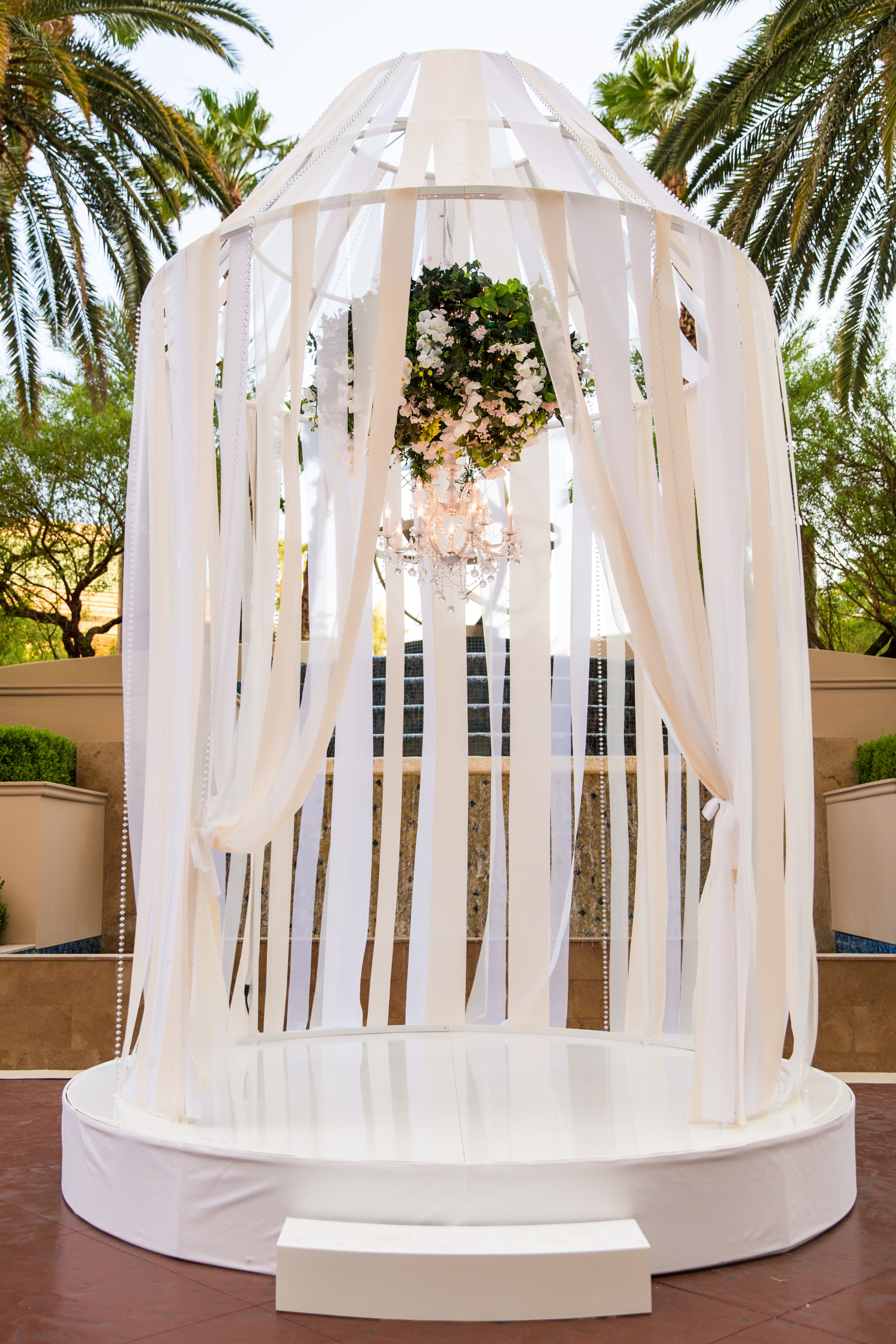 The wedding ceremony took place in a larger than life birdcage wrapped in ribbon with a floral chandelier hanging in the center.Wedding Planning by  Andrea Eppolito Events  · Photography by  Shandro Photo   · Wedding Venue  Four Seasons Las Vegas  · Floral and Decor by  Destination by Design  · Chandeliers and Lighting by  LED Unplugged