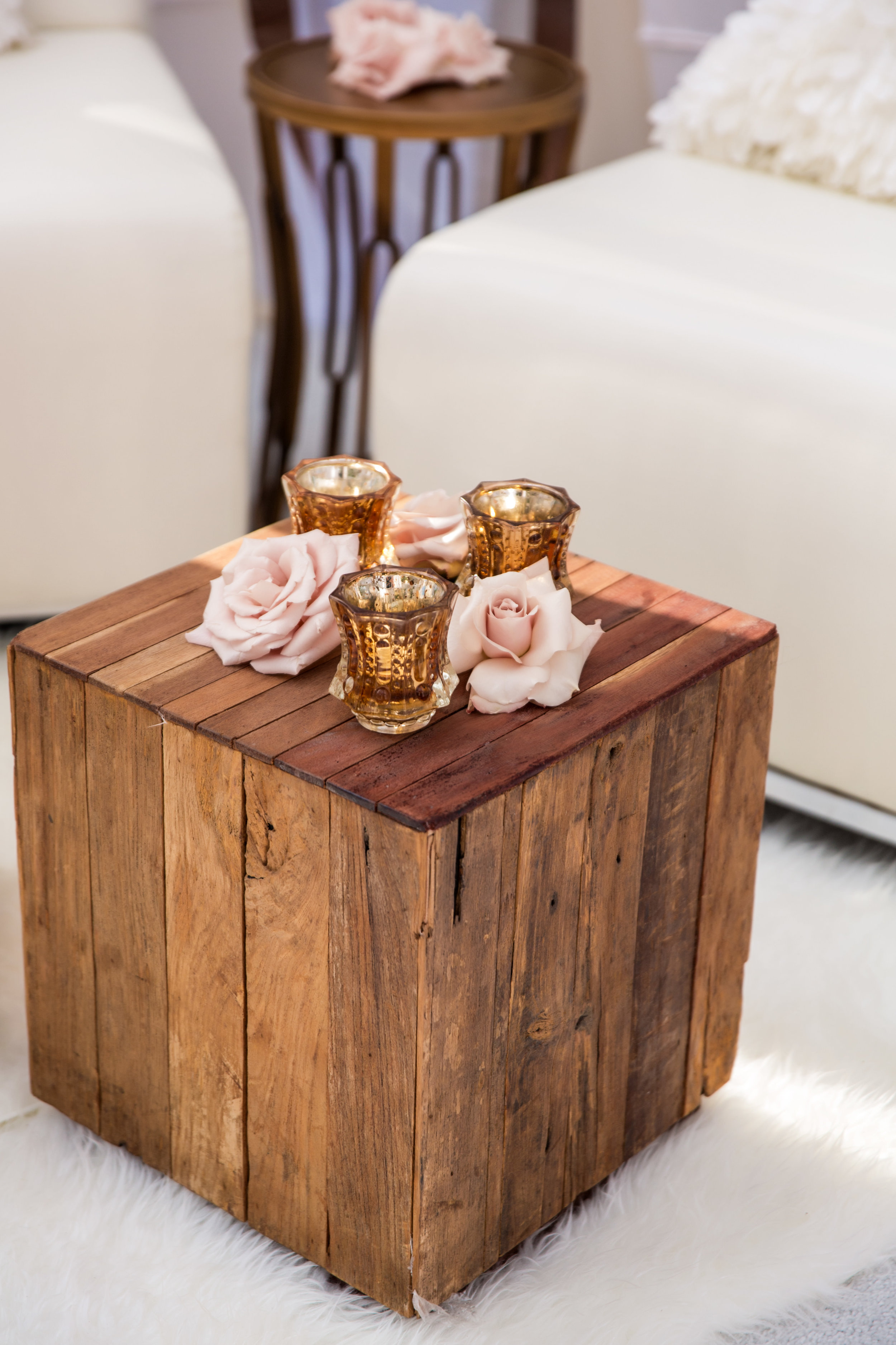 Wooden tables on fur rugs with mercury glass candle holders.Wedding Planning by  Andrea Eppolito Events  · Photography by  Shandro Photo   · Wedding Venue  Four Seasons Las Vegas  · Floral and Decor by  Destination by Design  · Chandeliers and Lighting by  LED Unplugged