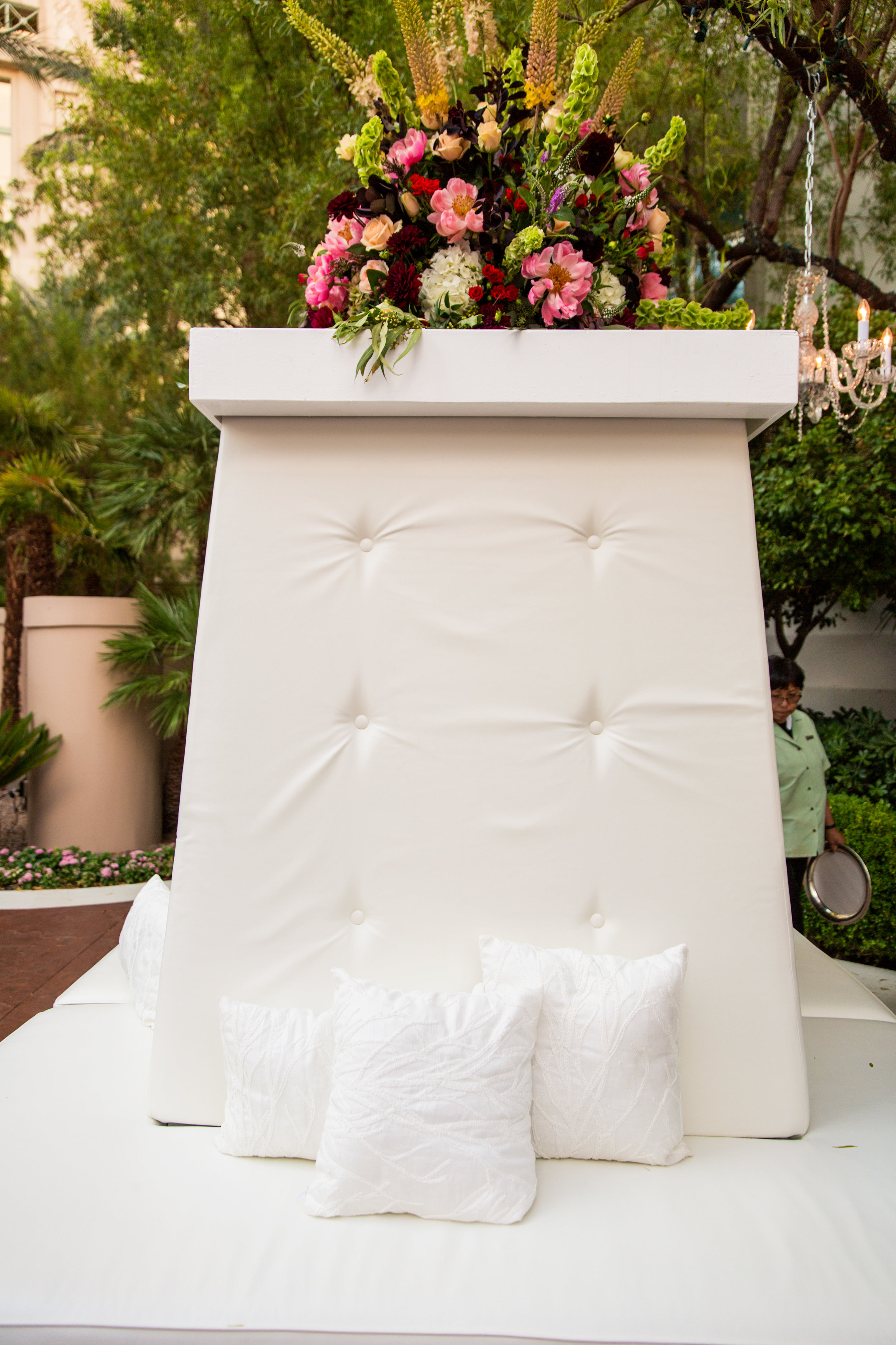 White tufted lounge furniture with red and fuchsia flowers.Wedding Planning by  Andrea Eppolito Events  · Photography by  Shandro Photo   · Wedding Venue  Four Seasons Las Vegas  · Floral and Decor by  Destination by Design  · Chandeliers and Lighting by  LED Unplugged