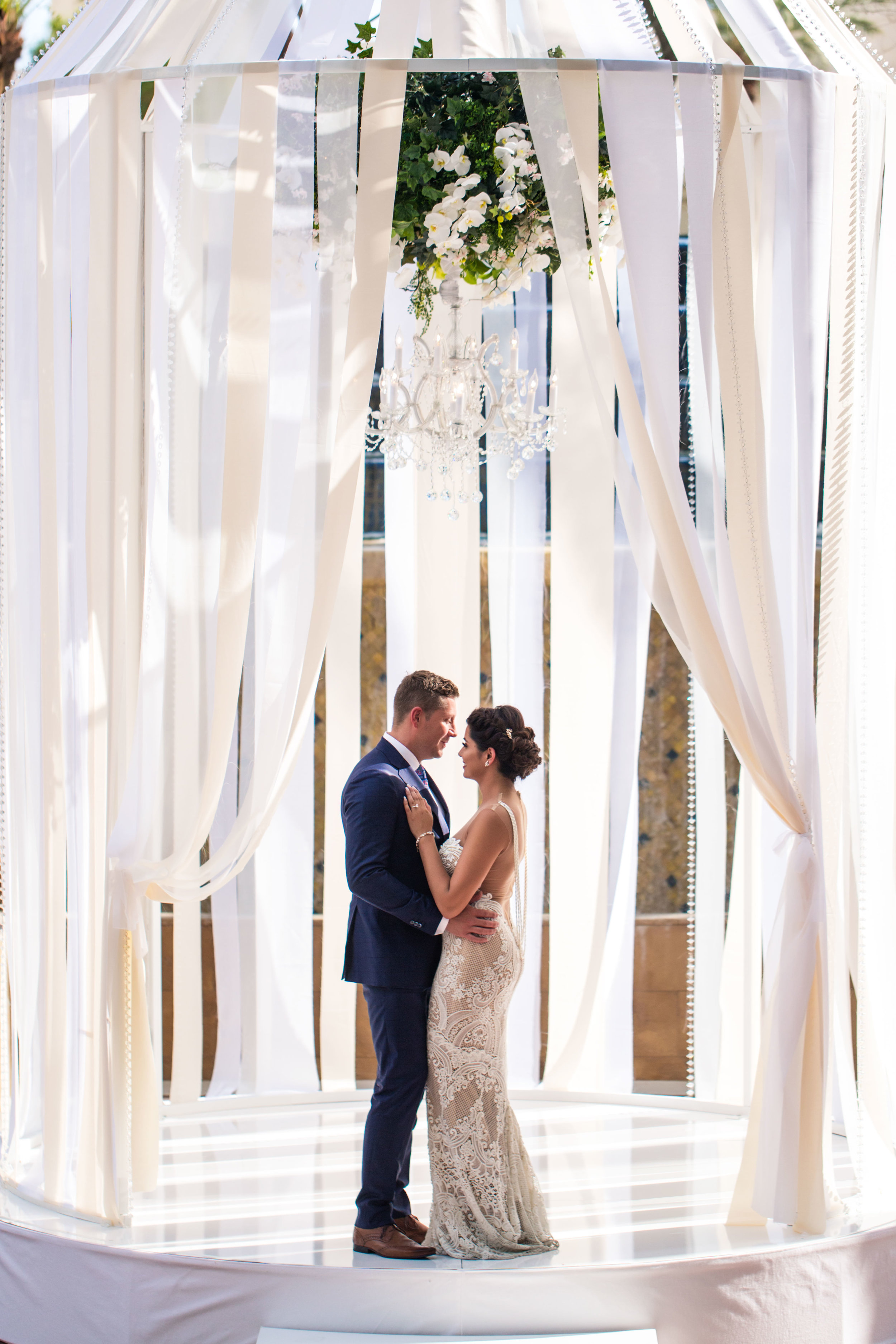 Bride and groom in birdcage under floral chandelier.Wedding Planning by  Andrea Eppolito Events  · Photography by  Shandro Photo   · Wedding Venue  Four Seasons Las Vegas  · Floral and Decor by  Destination by Design  · Cake by  Four Seasons Las Vegas  · Chandeliers and Lighting by  LED Unplugged  · Dress by  Berta