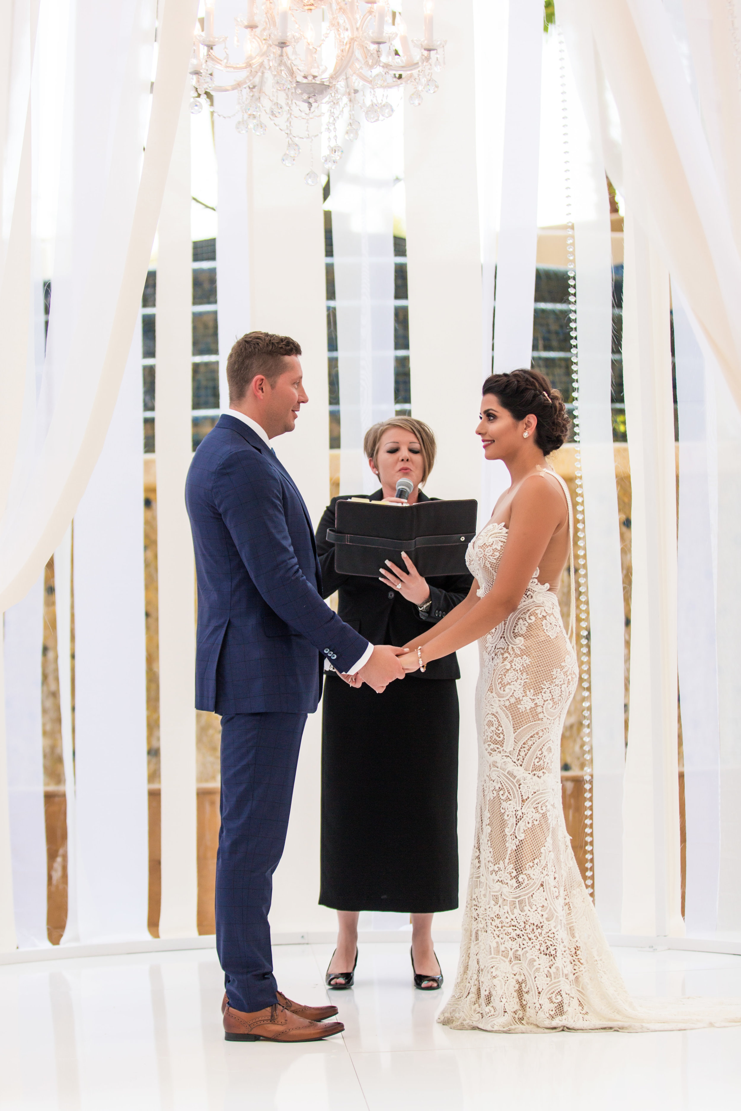 Wedding ceremony in birdcage.Wedding Planning by  Andrea Eppolito Events  · Photography by  Shandro Photo   · Wedding Venue  Four Seasons Las Vegas  · Floral and Decor by  Destination by Design  · Cake by  Four Seasons Las Vegas  · Chandeliers and Lighting by  LED Unplugged  · Dress by  Berta