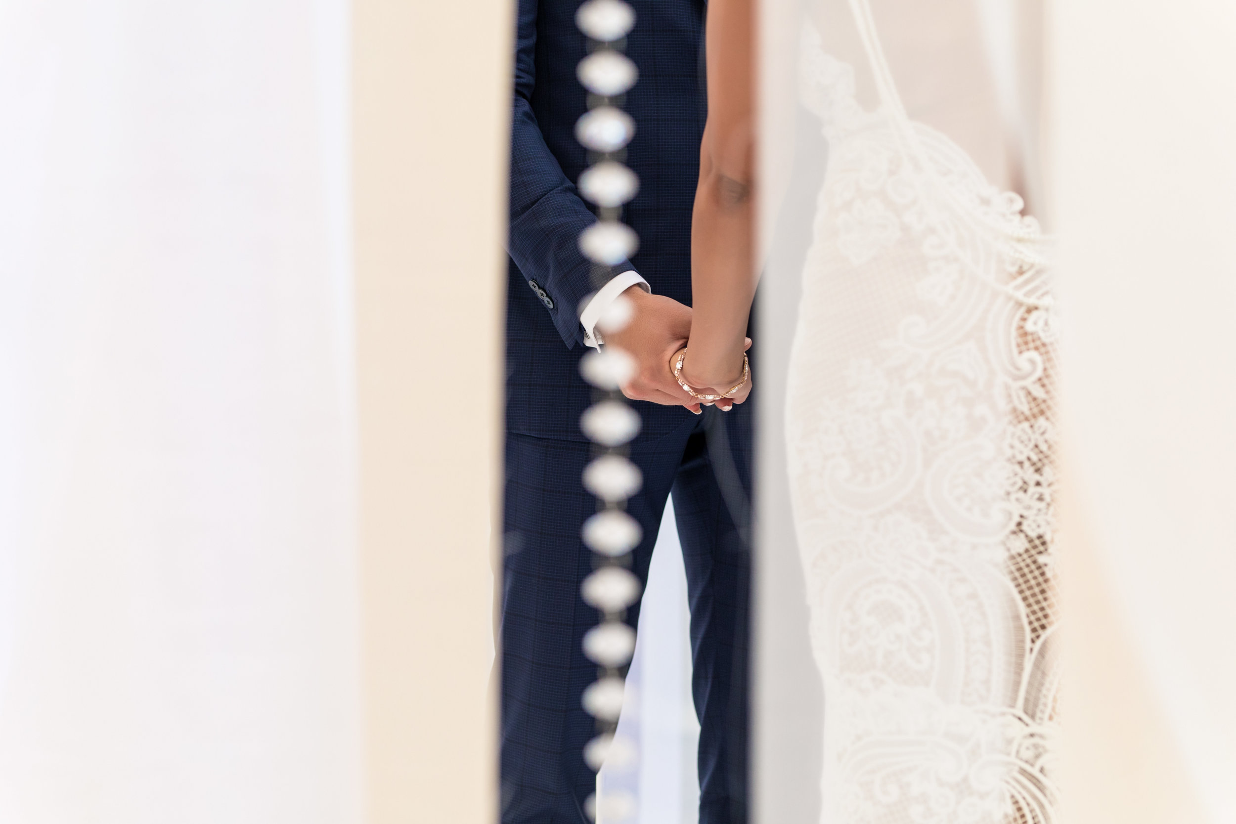 Holding hands in wedding ceremony.Wedding Planning by  Andrea Eppolito Events  · Photography by  Shandro Photo   · Wedding Venue  Four Seasons Las Vegas  · Floral and Decor by  Destination by Design  · Cake by  Four Seasons Las Vegas  · Chandeliers and Lighting by  LED Unplugged  · Dress by  Berta