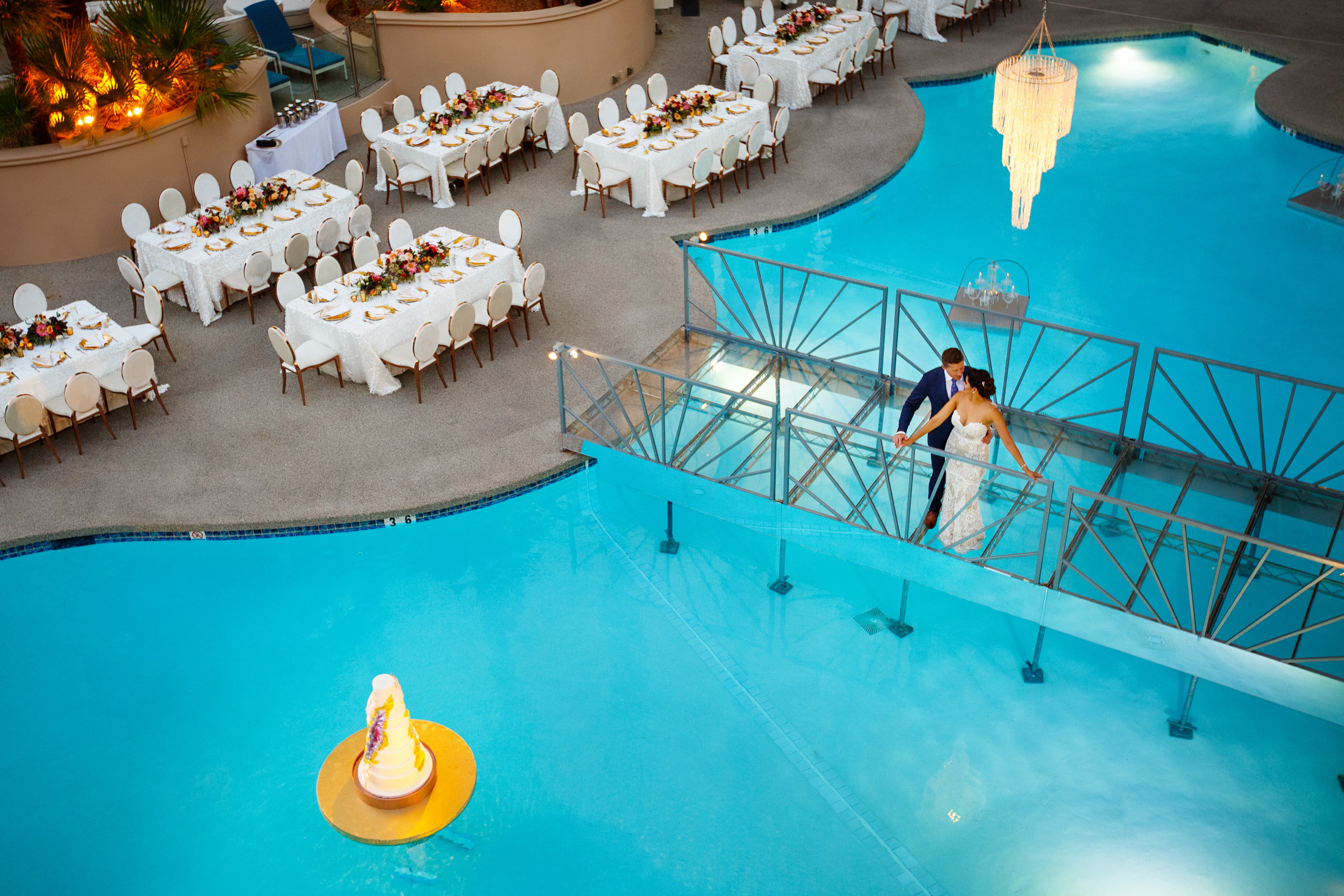 Bride & Groom on bridge over pool. Jewel toned wedding centerpieces with gold accents.Wedding Planning by  Andrea Eppolito Events  · Photography by  Shandro Photo   · Wedding Venue  Four Seasons Las Vegas  · Floral and Decor by  Destination by Design  · Cake by  Four Seasons Las Vegas  · Chandeliers and Lighting by  LED Unplugged  · Dress by  Berta  and Menu by Alligator Soup