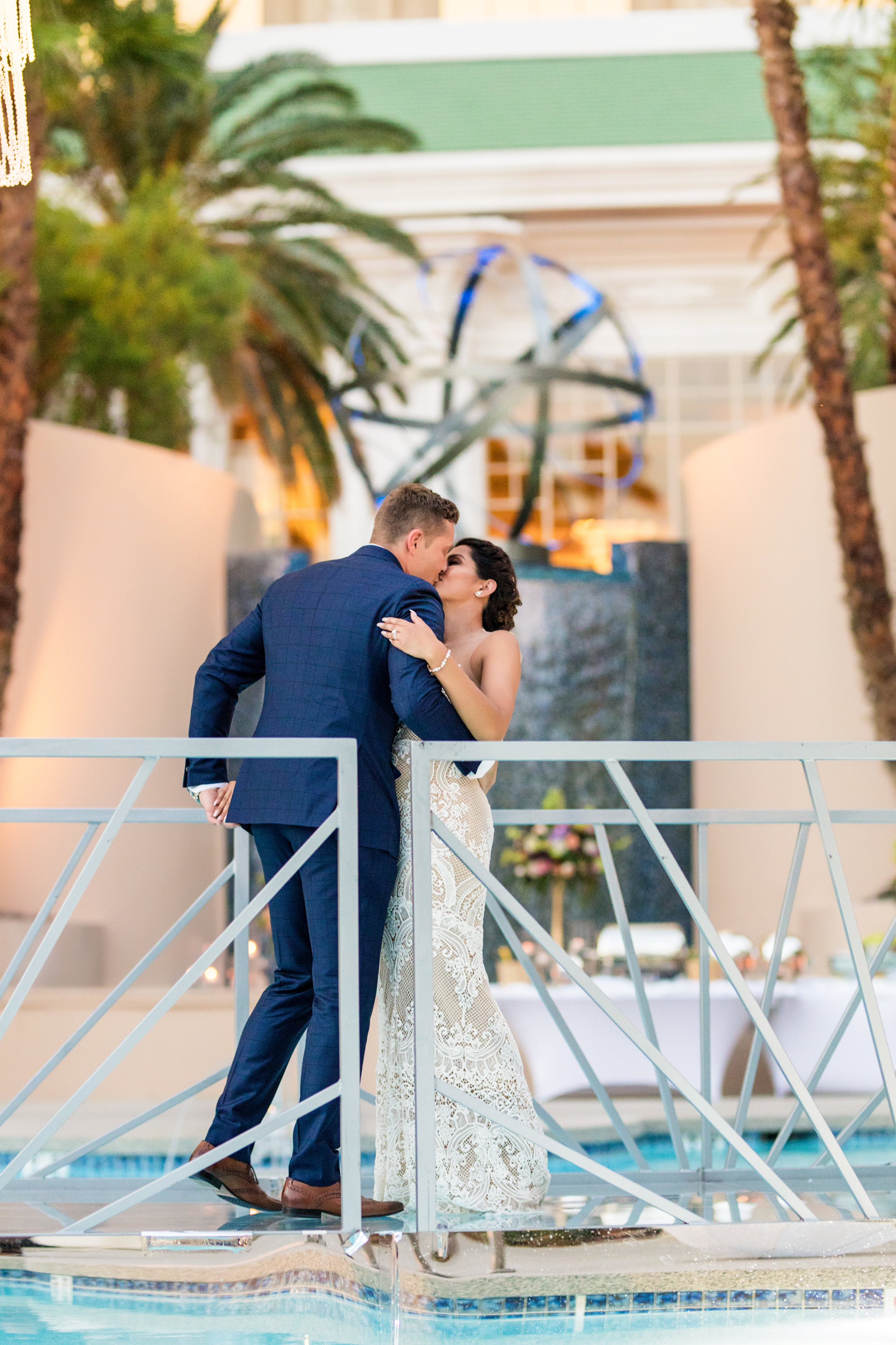 Bride and groom kiss on bridge over pool.Jewel toned wedding centerpieces with gold accents.Wedding Planning by  Andrea Eppolito Events  · Photography by  Shandro Photo   · Wedding Venue  Four Seasons Las Vegas  · Floral and Decor by  Destination by Design  · Cake by  Four Seasons Las Vegas  · Chandeliers and Lighting by  LED Unplugged  · Dress by  Berta  and Menu by Alligator Soup