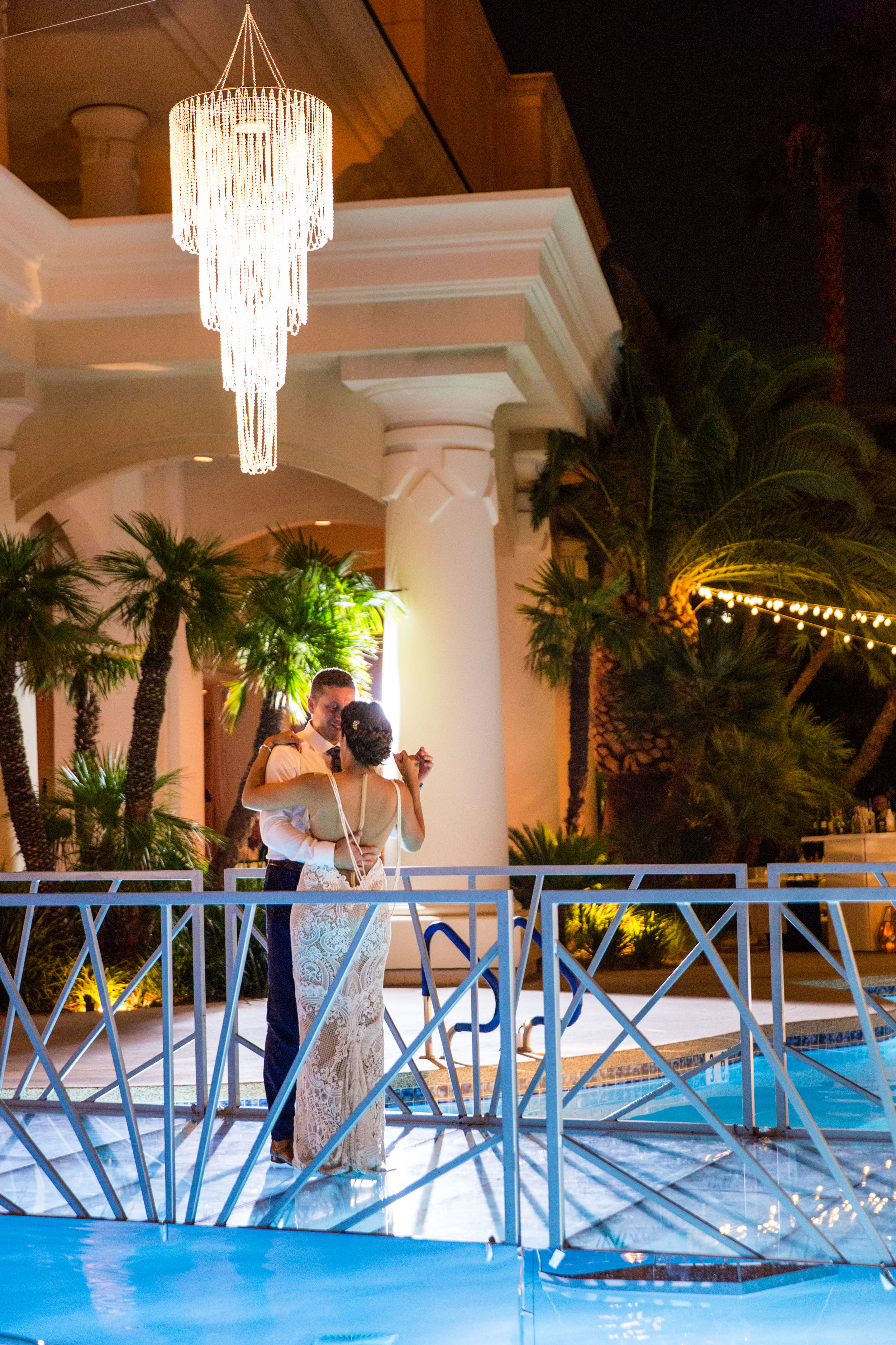 First dance on bridge over pool.Jewel toned wedding centerpieces with gold accents.Wedding Planning by  Andrea Eppolito Events  · Photography by  Shandro Photo   · Wedding Venue  Four Seasons Las Vegas  · Floral and Decor by  Destination by Design  · Cake by  Four Seasons Las Vegas  · Chandeliers and Lighting by  LED Unplugged  · Dress by  Berta  and Menu by Alligator Soup