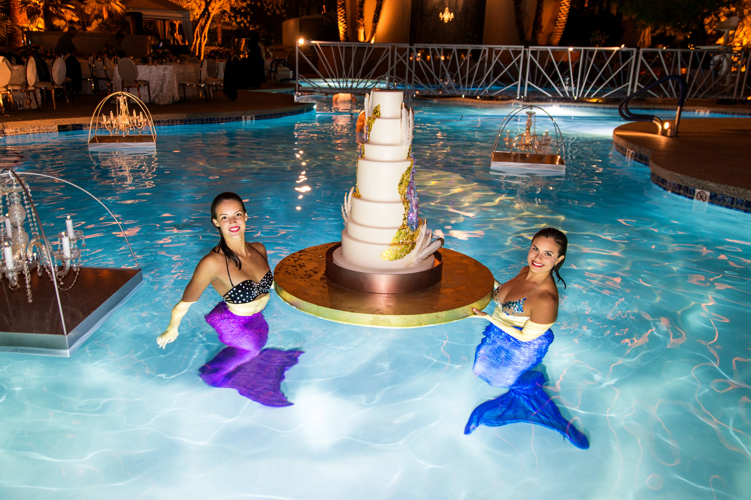 Mermaids with geode floating wedding cake.Wedding Planning by  Andrea Eppolito Events  · Photography by  Shandro Photo   · Wedding Venue  Four Seasons Las Vegas  · Floral and Decor by  Destination by Design  · Cake by  Four Seasons Las Vegas  · Chandeliers and Lighting by  LED Unplugged  · Dress by  Berta  and Menu by Alligator Soup