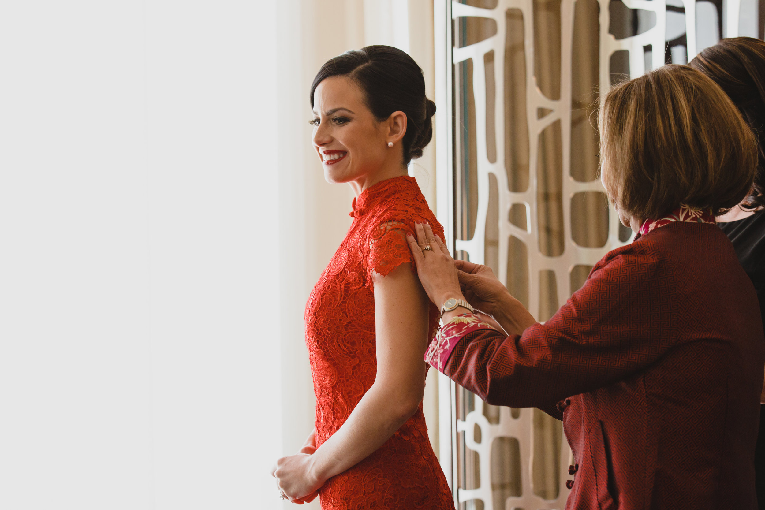 Being buttoned into red chinese lace dress. Luxury wedding at the Mandarin Oriental with a color scheme of white, blush, and pops of wine red produced by Las Vegas Wedding Planner Andrea Eppolito with photos by Stephen Salazar Photography.