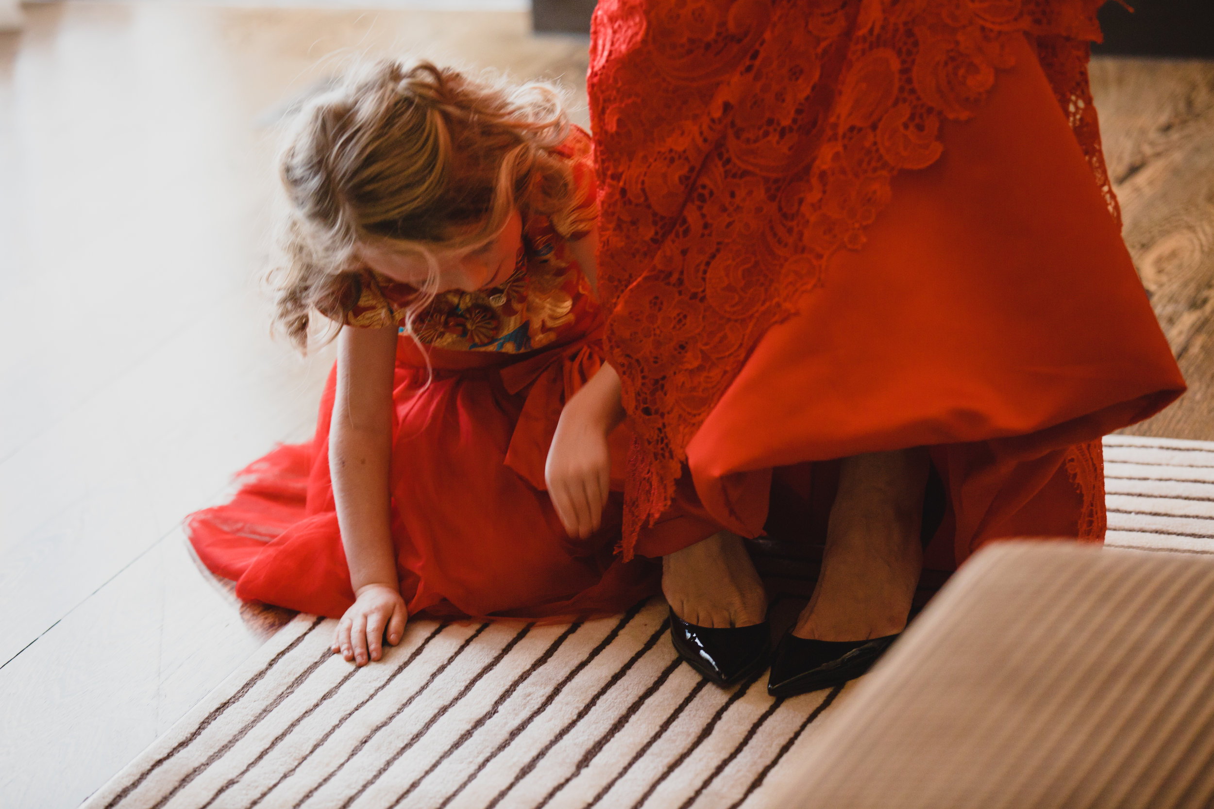 Flower girl helping bride into her black Louboutin shoes.Luxury wedding at the Mandarin Oriental with a color scheme of white, blush, and pops of wine red produced by Las Vegas Wedding Planner Andrea Eppolito with photos by Stephen Salazar Photography.