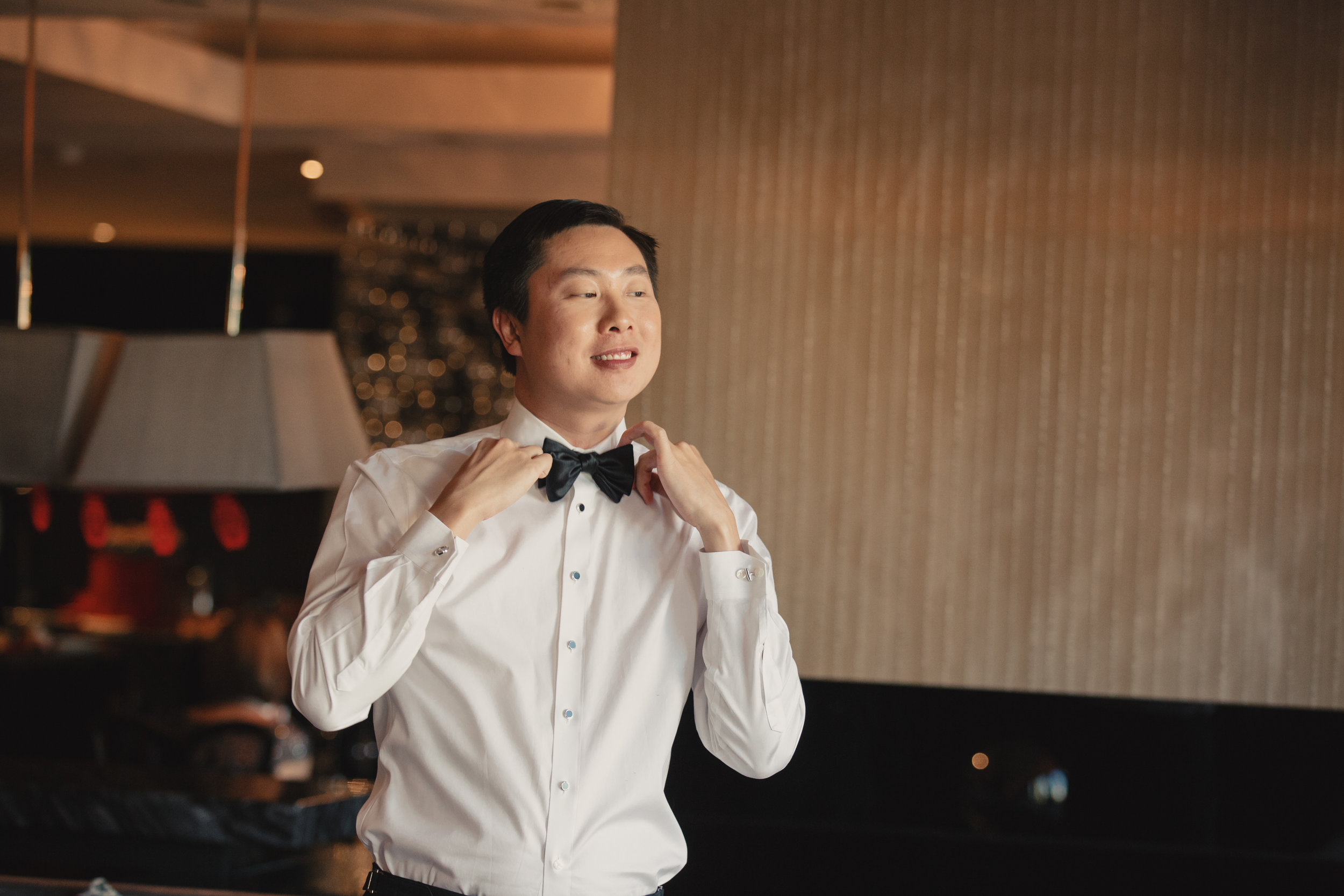 Groom putting on bowtie.Luxury wedding at the Mandarin Oriental with a color scheme of white, blush, and pops of wine red produced by Las Vegas Wedding Planner Andrea Eppolito with photos by Stephen Salazar Photography.