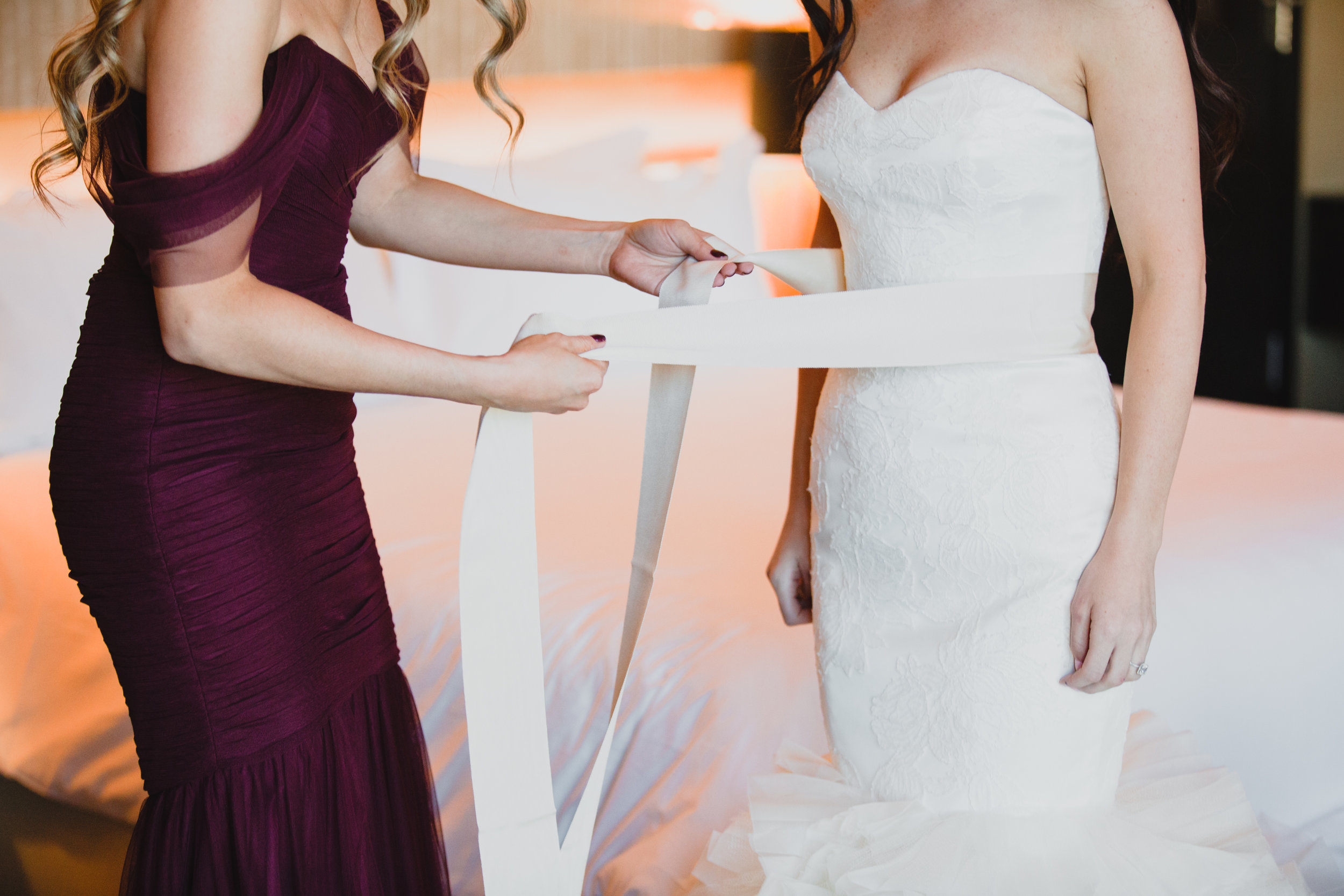Tie on belt for the Vera Wang Wedding Dress.Luxury wedding at the Mandarin Oriental with a color scheme of white, blush, and pops of wine red produced by Las Vegas Wedding Planner Andrea Eppolito with photos by Stephen Salazar Photography.