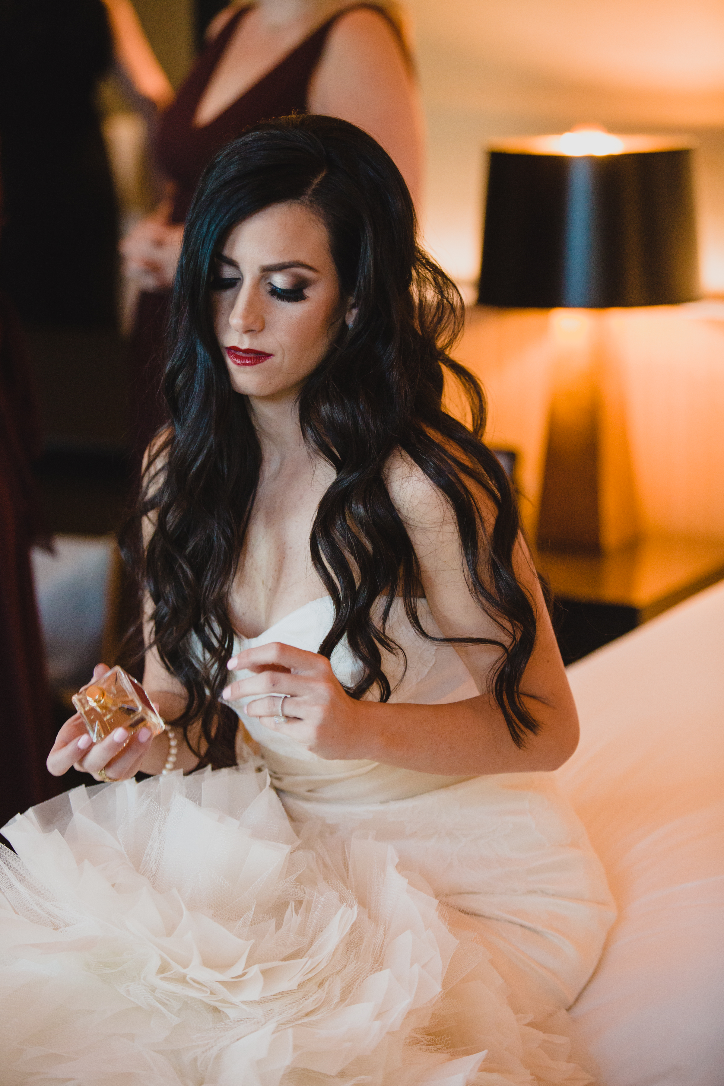 Bride spraying perfume.Luxury wedding at the Mandarin Oriental with a color scheme of white, blush, and pops of wine red produced by Las Vegas Wedding Planner Andrea Eppolito with photos by Stephen Salazar Photography.
