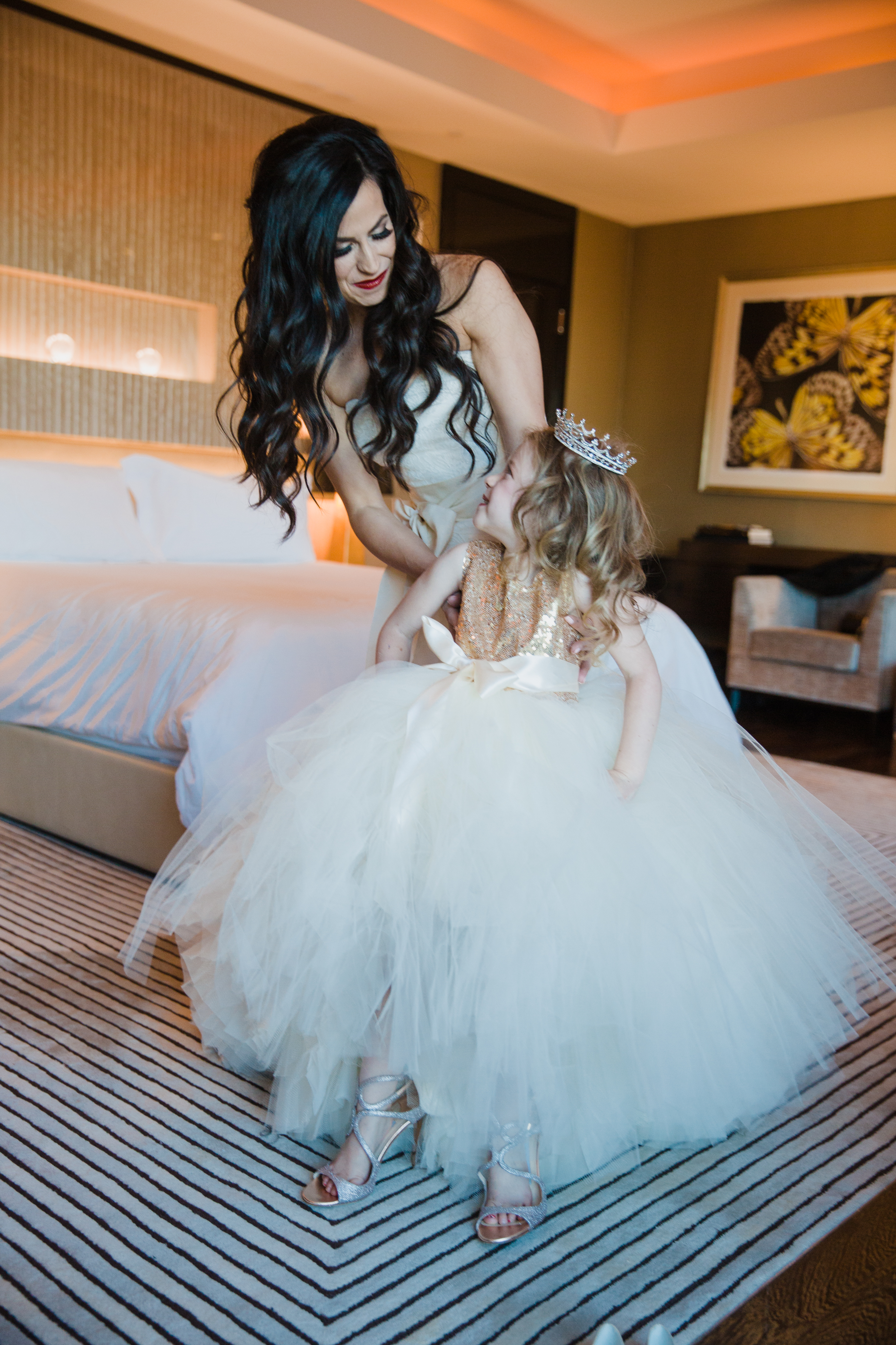 Flower girl wearing bride's wedding shoes.Luxury wedding at the Mandarin Oriental with a color scheme of white, blush, and pops of wine red produced by Las Vegas Wedding Planner Andrea Eppolito with photos by Stephen Salazar Photography.