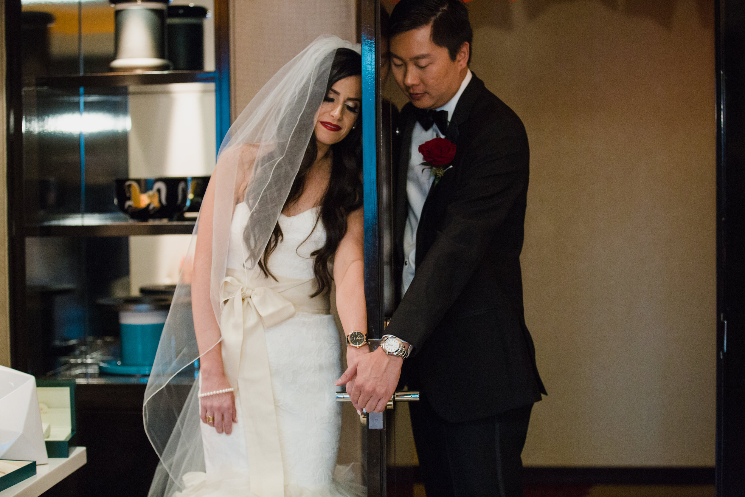 First touch wearing rolex watches.Luxury wedding at the Mandarin Oriental with a color scheme of white, blush, and pops of wine red produced by Las Vegas Wedding Planner Andrea Eppolito with photos by Stephen Salazar Photography.