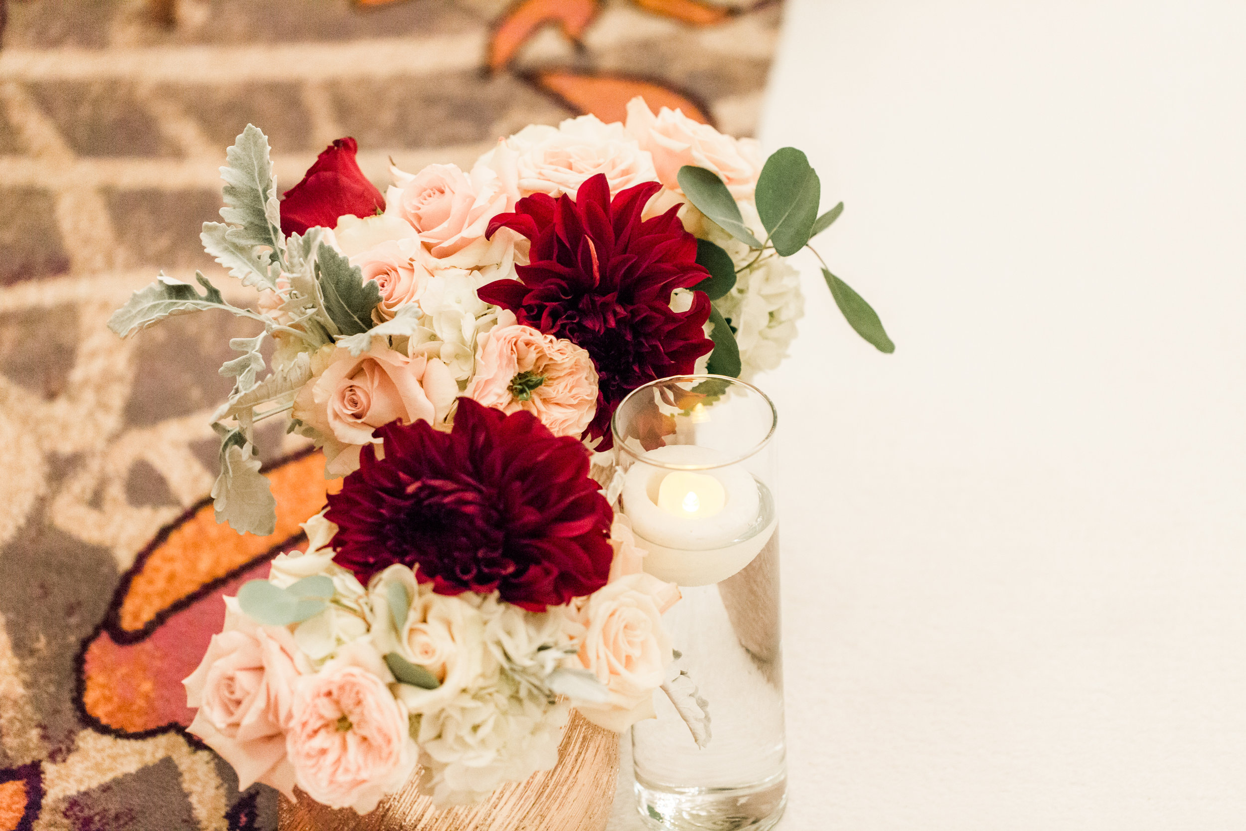 Red and pink wedding ceremony flowers.Luxury wedding at the Mandarin Oriental with a color scheme of white, blush, and pops of wine red produced by Las Vegas Wedding Planner Andrea Eppolito with photos by Stephen Salazar Photography.
