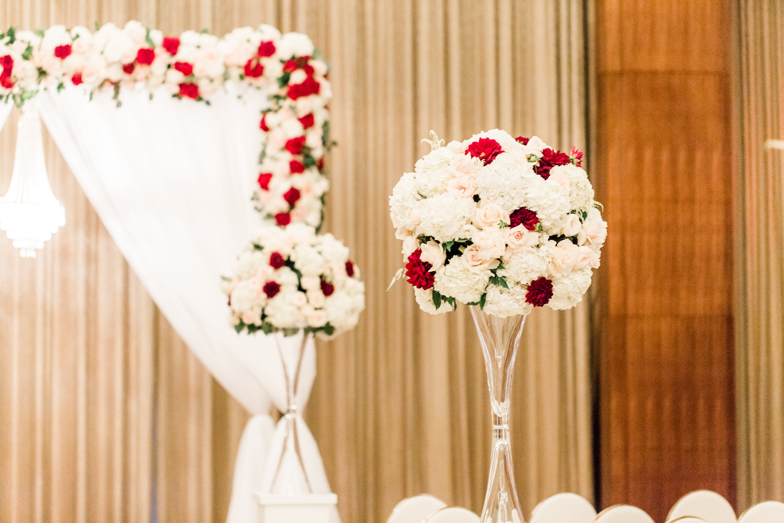 Pink and white with pops of red wedding flowers.Luxury wedding at the Mandarin Oriental with a color scheme of white, blush, and pops of wine red produced by Las Vegas Wedding Planner Andrea Eppolito with photos by Stephen Salazar Photography.