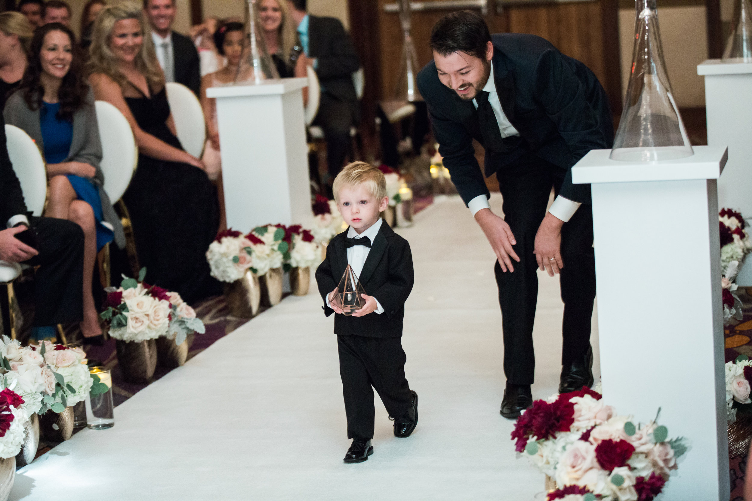 Ring bearer in gold and glass.Luxury wedding at the Mandarin Oriental with a color scheme of white, blush, and pops of wine red produced by Las Vegas Wedding Planner Andrea Eppolito with photos by Stephen Salazar Photography.