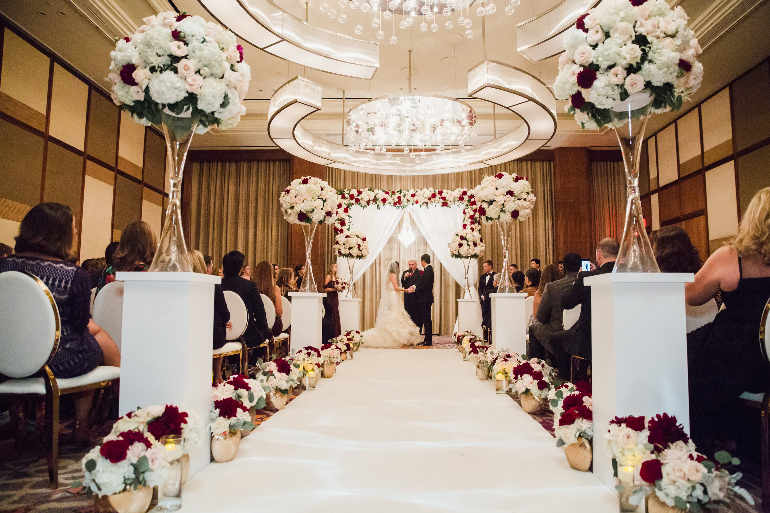 Wedding ceremony.Luxury wedding at the Mandarin Oriental with a color scheme of white, blush, and pops of wine red produced by Las Vegas Wedding Planner Andrea Eppolito with photos by Stephen Salazar Photography.