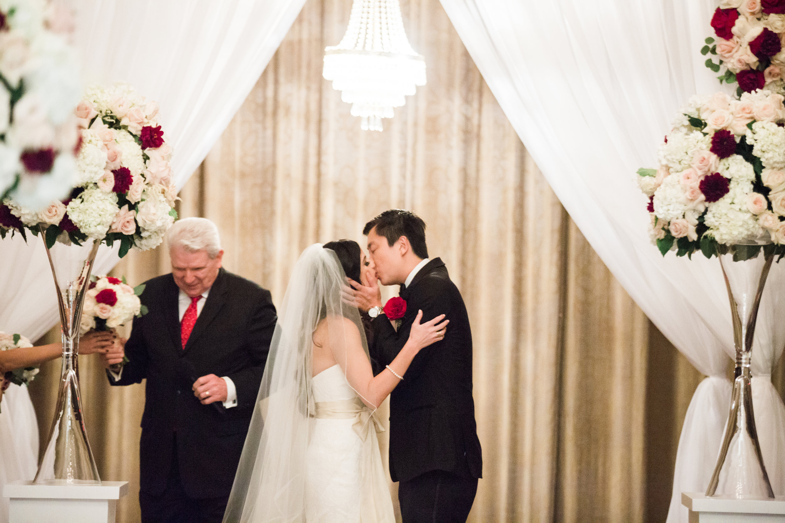 First Kiss at wedding ceremony.Luxury wedding at the Mandarin Oriental with a color scheme of white, blush, and pops of wine red produced by Las Vegas Wedding Planner Andrea Eppolito with photos by Stephen Salazar Photography.