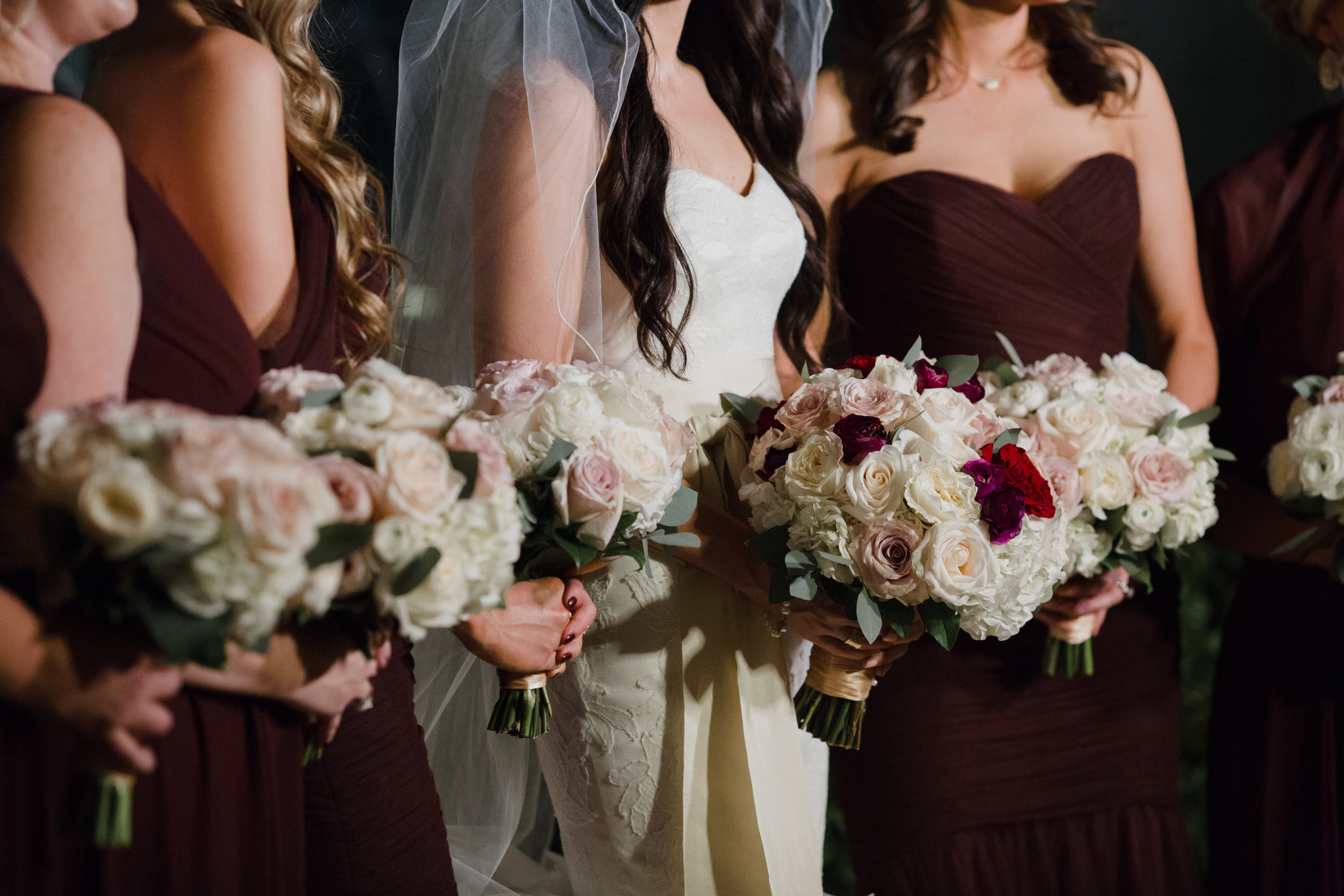 Bridesmaids bouquets in ivor and burgandy.Luxury wedding at the Mandarin Oriental with a color scheme of white, blush, and pops of wine red produced by Las Vegas Wedding Planner Andrea Eppolito with photos by Stephen Salazar Photography.