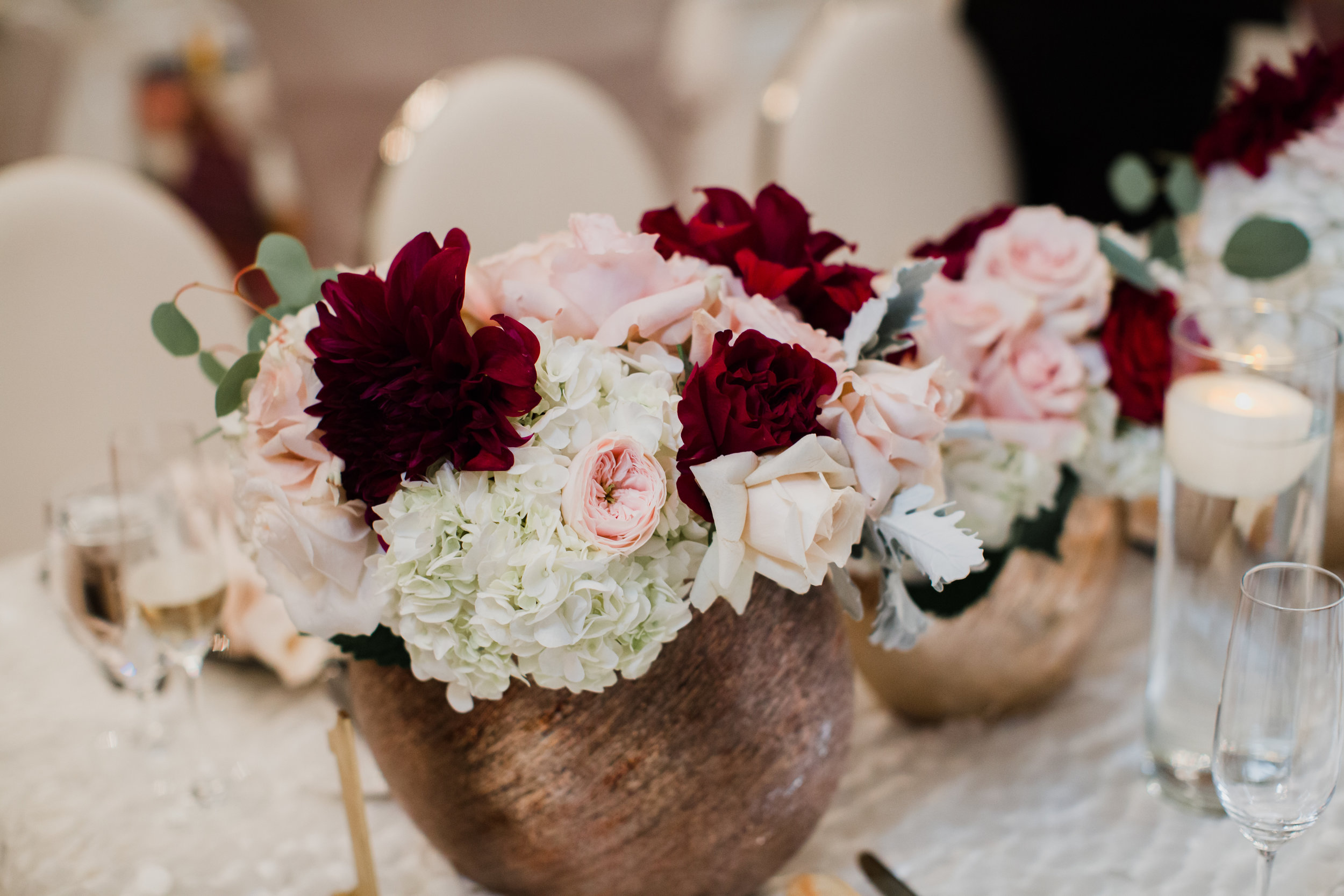 Dark red and pink roses in wedding centerpieces.Luxury wedding at the Mandarin Oriental with a color scheme of white, blush, and pops of wine red produced by Las Vegas Wedding Planner Andrea Eppolito with photos by Stephen Salazar Photography.