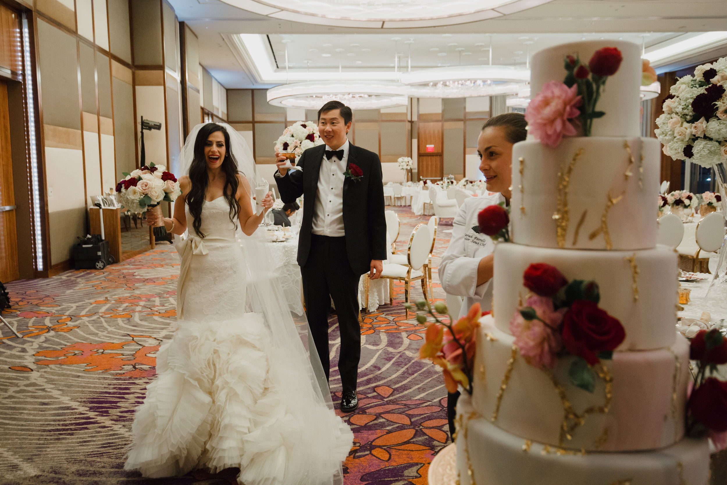 Wedding Cake Reveal.Luxury wedding at the Mandarin Oriental with a color scheme of white, blush, and pops of wine red produced by Las Vegas Wedding Planner Andrea Eppolito with photos by Stephen Salazar Photography.
