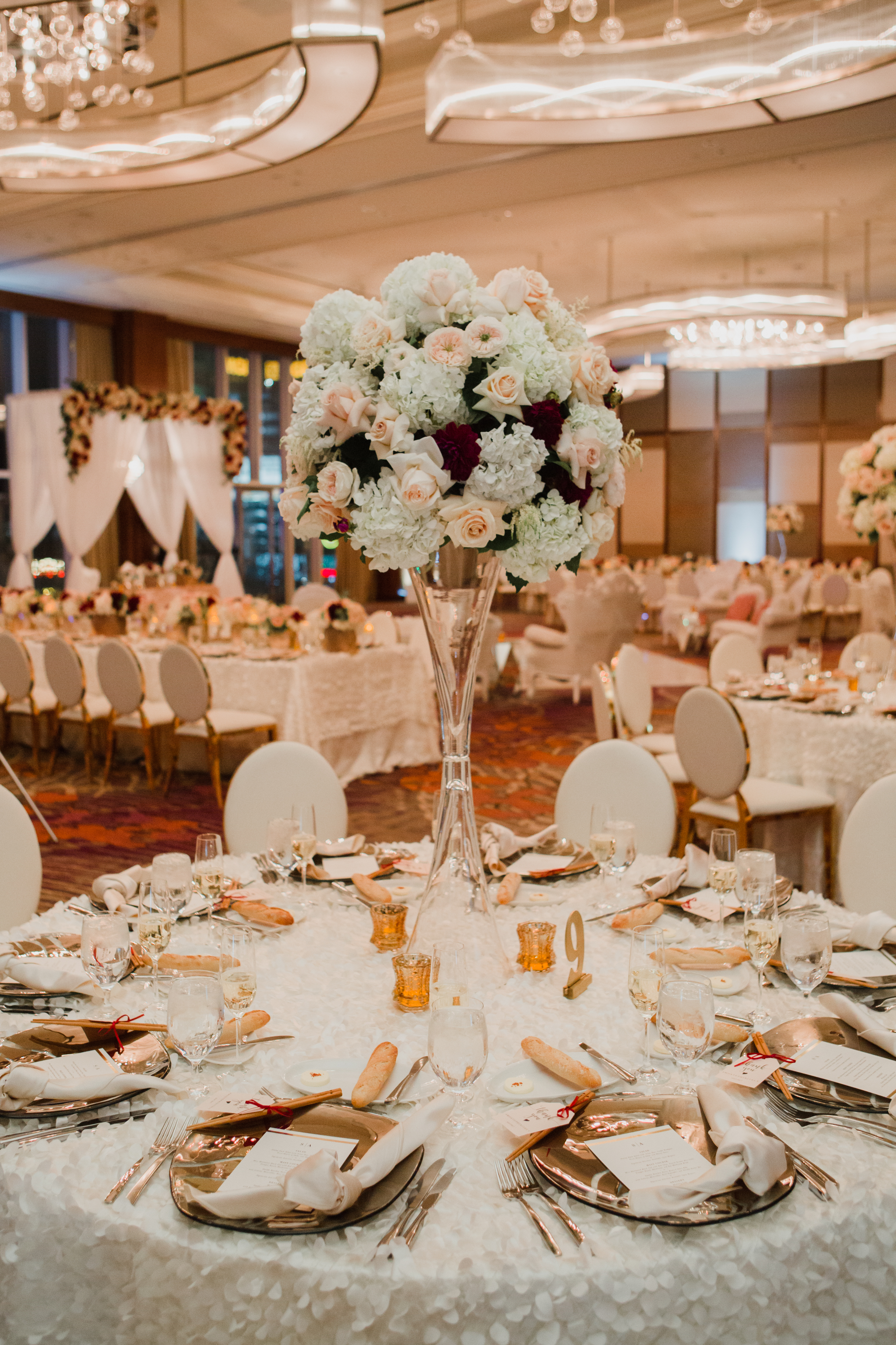 Ivory large centerpieces with dark red pops of color.Luxury wedding at the Mandarin Oriental with a color scheme of white, blush, and pops of wine red produced by Las Vegas Wedding Planner Andrea Eppolito with photos by Stephen Salazar Photography.