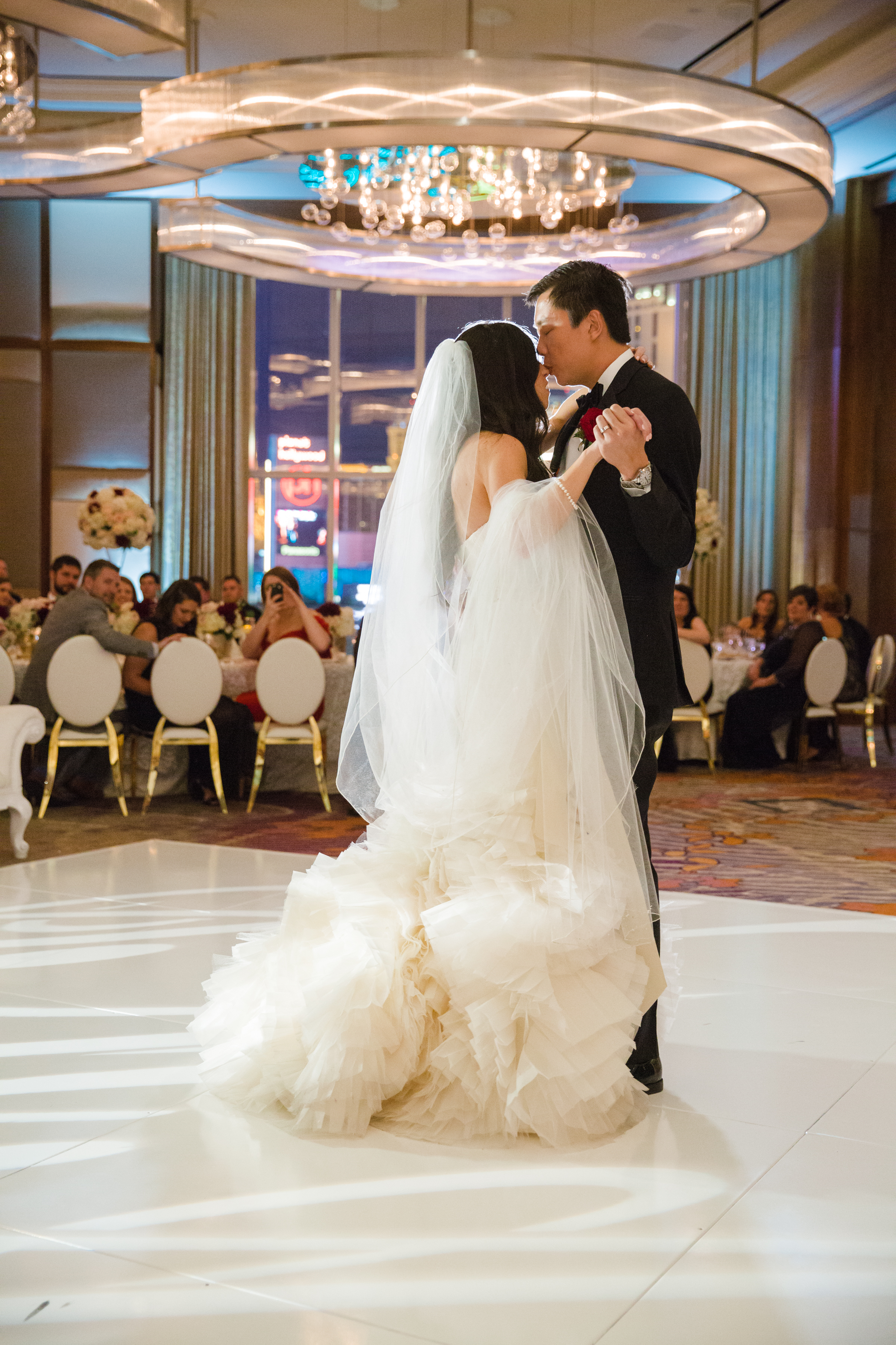 First dance on high gloss white dance floor. Bride in Vera Wang with beautiful veil.Luxury wedding at the Mandarin Oriental with a color scheme of white, blush, and pops of wine red produced by Las Vegas Wedding Planner Andrea Eppolito with photos by Stephen Salazar Photography.