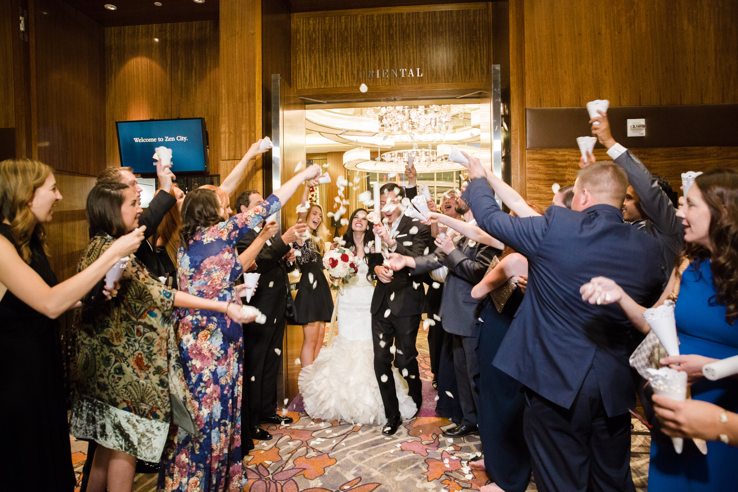 Guests throwing rose petals during bride and groom's exit.Luxury wedding at the Mandarin Oriental with a color scheme of white, blush, and pops of wine red produced by Las Vegas Wedding Planner Andrea Eppolito with photos by Stephen Salazar Photography.