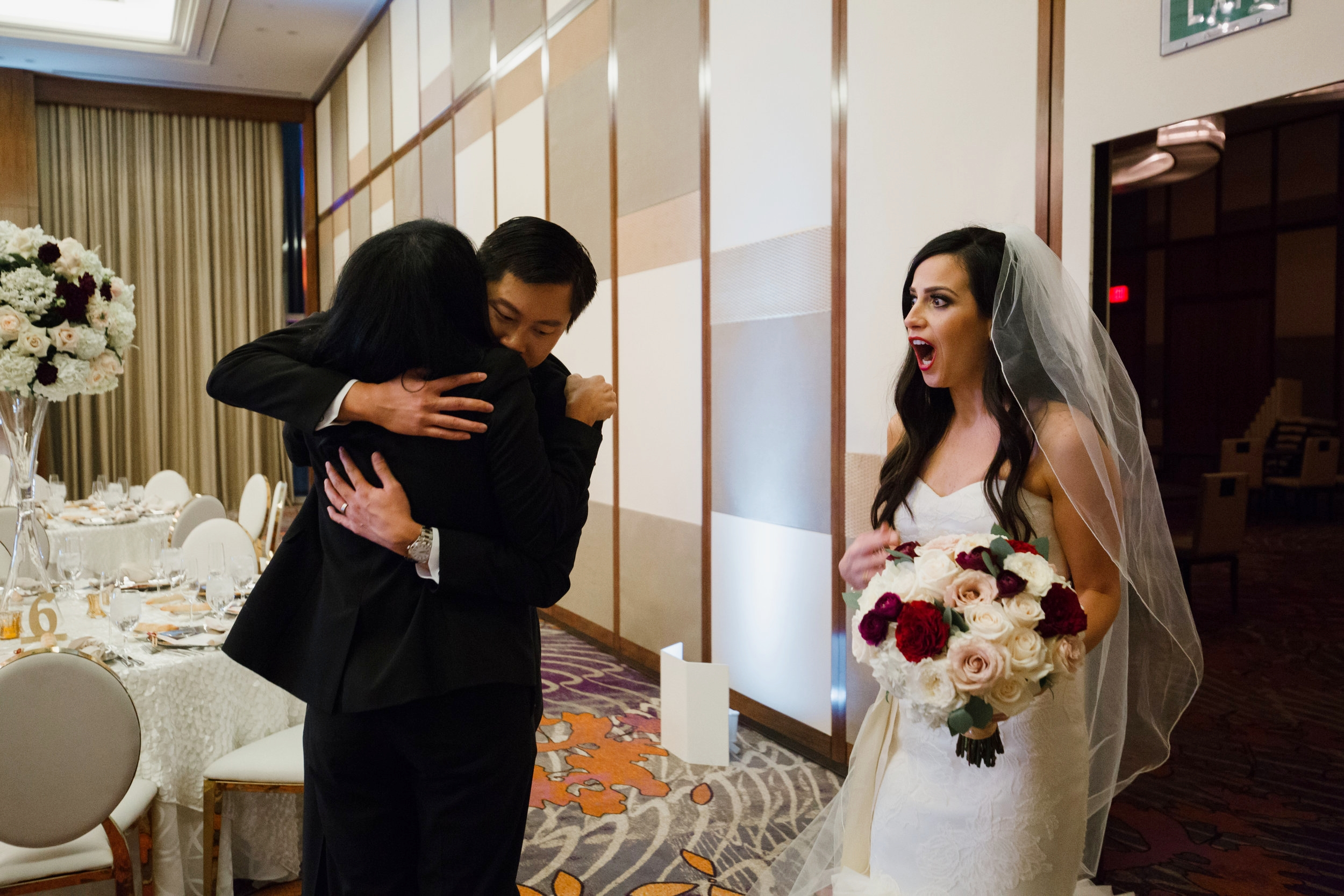 Reception reveal. Bride sees the ballroom for the first time.Luxury wedding at the Mandarin Oriental with a color scheme of white, blush, and pops of wine red produced by Las Vegas Wedding Planner Andrea Eppolito with photos by Stephen Salazar Photography.