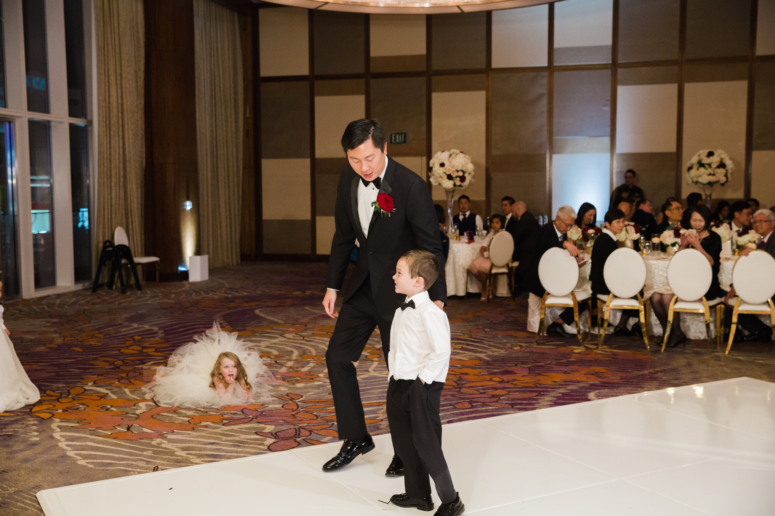 Ring bearer on the dance floor.Luxury wedding at the Mandarin Oriental with a color scheme of white, blush, and pops of wine red produced by Las Vegas Wedding Planner Andrea Eppolito with photos by Stephen Salazar Photography.