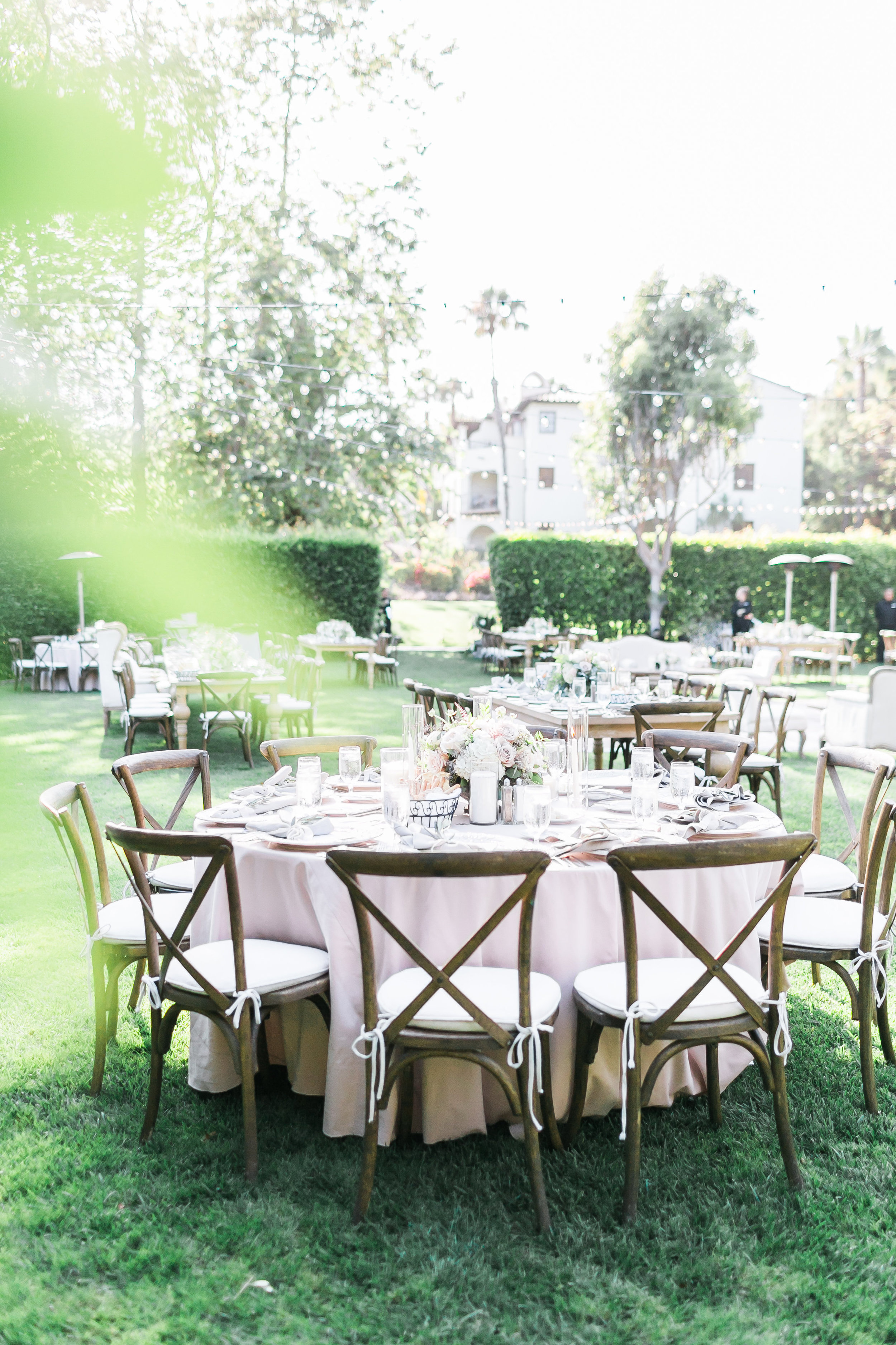 Outdoor garden wedding surrounded by hedges, with wooden tables and chairs.     Destination Wedding Planner  ANDREA EPPOLITO EVENTS  · Images by  J.ANNE P  HOTOOGRAPHY  · Video  HOO FILMS  · Venue Ritz Carlton Bacara Santa Barbara ·Gown MONIQUE LHULLIER ·Bridesmaids Dresses  SHOW ME YOUR MUMU ·Stationery  SHE PAPERIE ·Bride's Shoes  BADGLEY MISCHKA ·Hair and Makeup  TEAM HAIR AND MAKEUP · Floral  BLUE MAGNOLIA ·Linen  LA TAVOLA ·Decor Rentals  TENT MERCHANT ·Calligraphy  EBB ·Lighting  FIVE STAR AV ·Ice Cream Station  MCCONNELL'S ICE CREAM