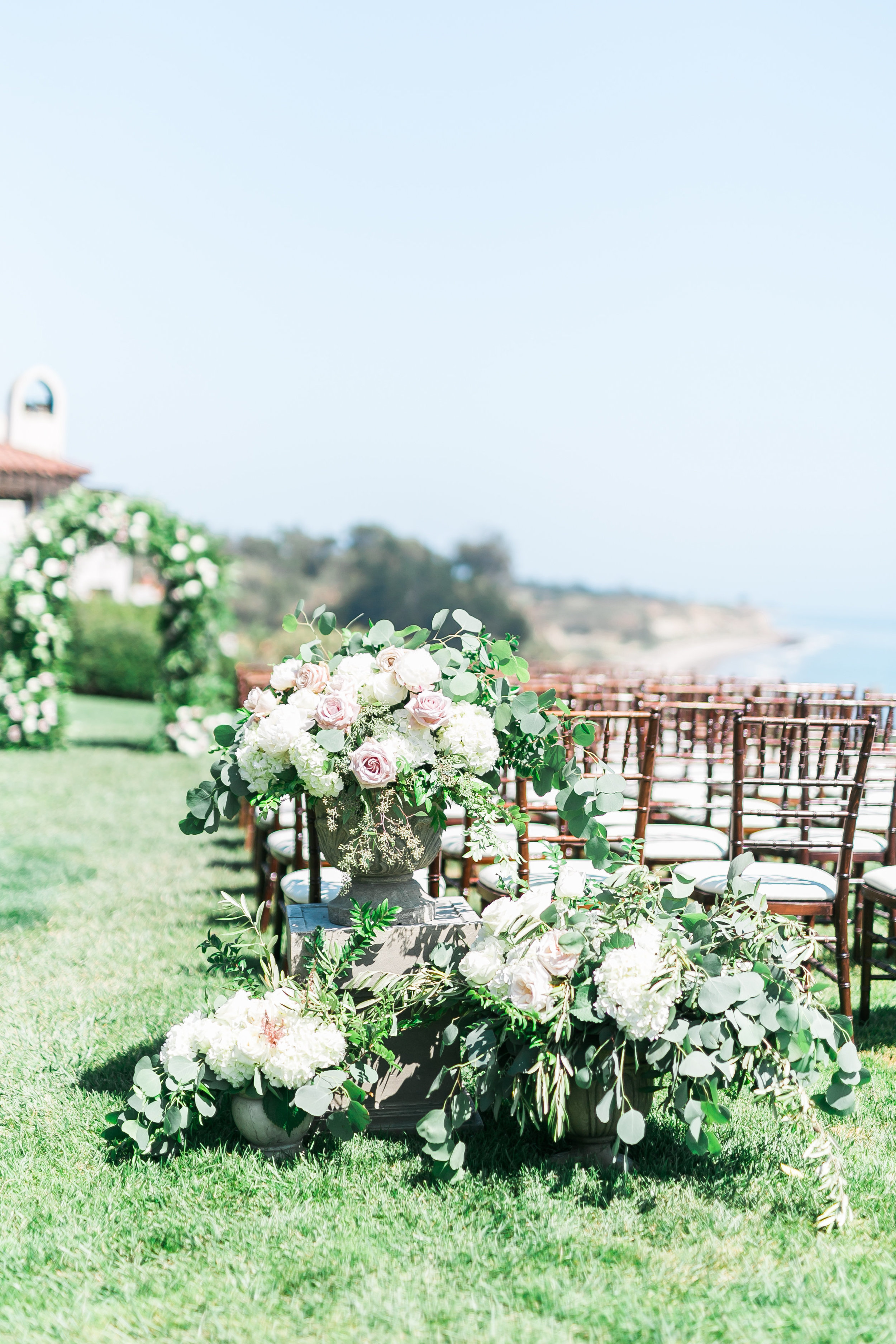 Outdoor wedding at The Bacara Santa Barbara.   CREDITS:  Destination Wedding Planner  ANDREA EPPOLITO EVENTS  · Images by  J.ANNE P  HOTOGRAPHY  · Video  HOO FILMS  · Venue Ritz Carlton Bacara Santa Barbara ·Gown  MONIQUE LHULLIER ·Bridesmaids Dresses  SHOW ME YOUR MUMU ·Stationery  SHE PAPERIE ·Bride's Shoes  BADGLEY MISCHKA ·Hair and Makeup  TEAM HAIR AND MAKEUP · Floral  BLUE MAGNOLIA ·Linen  LA TAVOLA ·Decor Rentals  TENT MERCHANT ·Calligraphy  EBB ·Lighting  FIVE STAR AV ·Ice Cream Station  MCCONNELL'S ICE CREAM