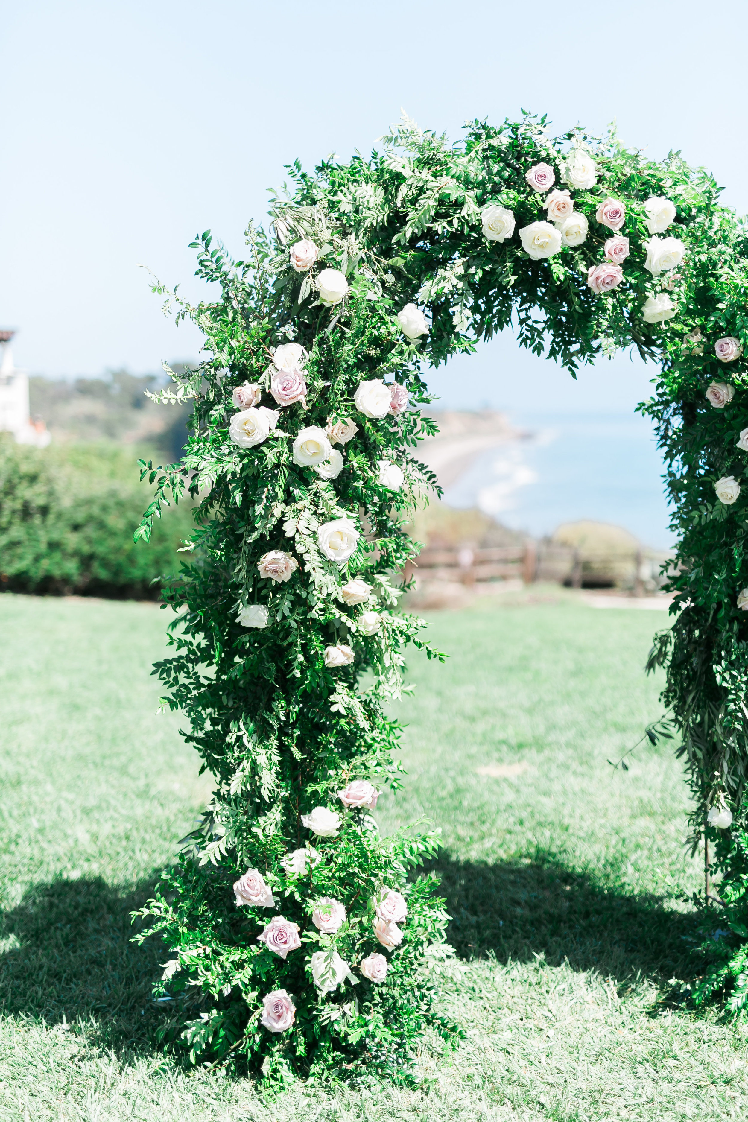 Ceremony arch at The Ritz Carlton Bacara Santa Barbara.   CREDITS:  Destination Wedding Planner  ANDREA EPPOLITO EVENTS  · Images by  J.ANNE P  HOTOGRAPHY  · Video  HOO FILMS  · Venue Ritz Carlton Bacara Santa Barbara ·Gown  MONIQUE LHULLIER ·Bridesmaids Dresses  SHOW ME YOUR MUMU ·Stationery  SHE PAPERIE ·Bride's Shoes  BADGLEY MISCHKA ·Hair and Makeup  TEAM HAIR AND MAKEUP · Floral  BLUE MAGNOLIA ·Linen  LA TAVOLA ·Decor Rentals  TENT MERCHANT ·Calligraphy  EBB ·Lighting  FIVE STAR AV ·Ice Cream Station  MCCONNELL'S ICE CREAM