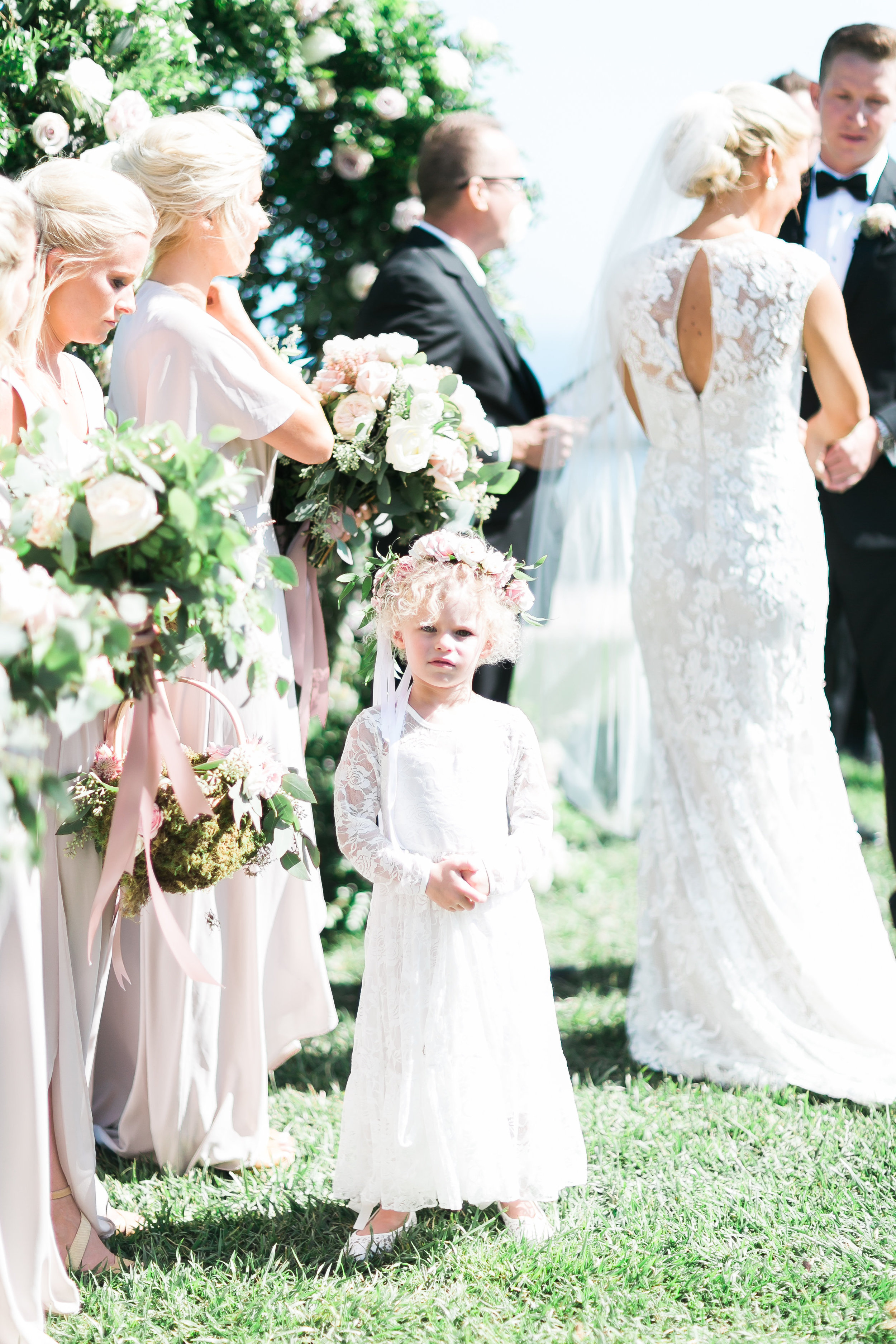 Flower girl in lace dress at wedding ceremony.   CREDITS:  Destination Wedding Planner  ANDREA EPPOLITO EVENTS  · Images by  J.ANNE P  HOTOGRAPHY  · Video  HOO FILMS  · Venue Ritz Carlton Bacara Santa Barbara ·Gown  MONIQUE LHULLIER ·Bridesmaids Dresses  SHOW ME YOUR MUMU ·Stationery  SHE PAPERIE ·Bride's Shoes  BADGLEY MISCHKA ·Hair and Makeup  TEAM HAIR AND MAKEUP · Floral  BLUE MAGNOLIA ·Linen  LA TAVOLA ·Decor Rentals  TENT MERCHANT ·Calligraphy  EBB ·Lighting  FIVE STAR AV ·Ice Cream Station  MCCONNELL'S ICE CREAM