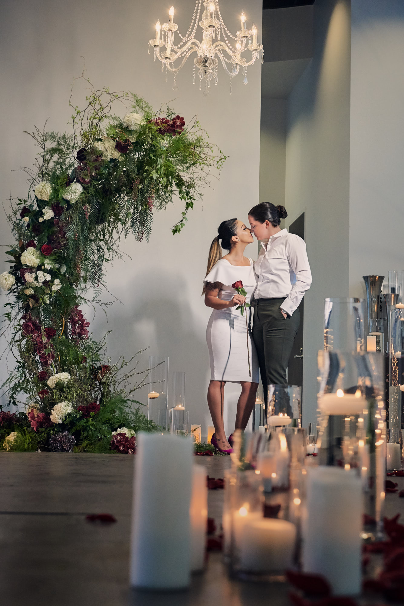 Two Brides Kissing.   Las Vegas Wedding Planner Andrea Eppolito designed the surprise engagement at the Mandarin Oriental for two brides to be.  Decor and lighting by Flora Couture and LED Unplugged, with photos by Fabio and Adri.