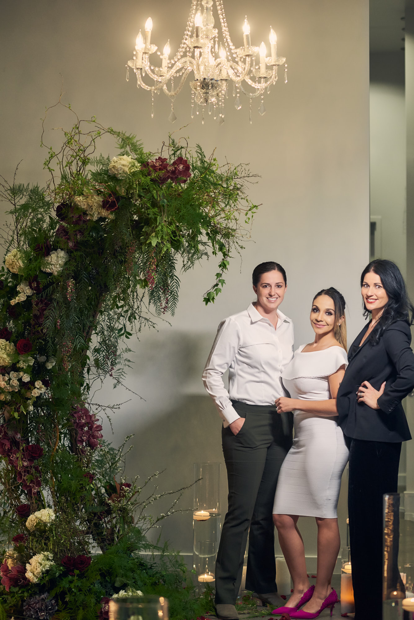 Two brides with Proposal Planner Andrea Eppolito.  Las Vegas Wedding Planner Andrea Eppolito designed the surprise engagement at the Mandarin Oriental for two brides to be.  Decor and lighting by Flora Couture and LED Unplugged, with photos by Fabio and Adri.