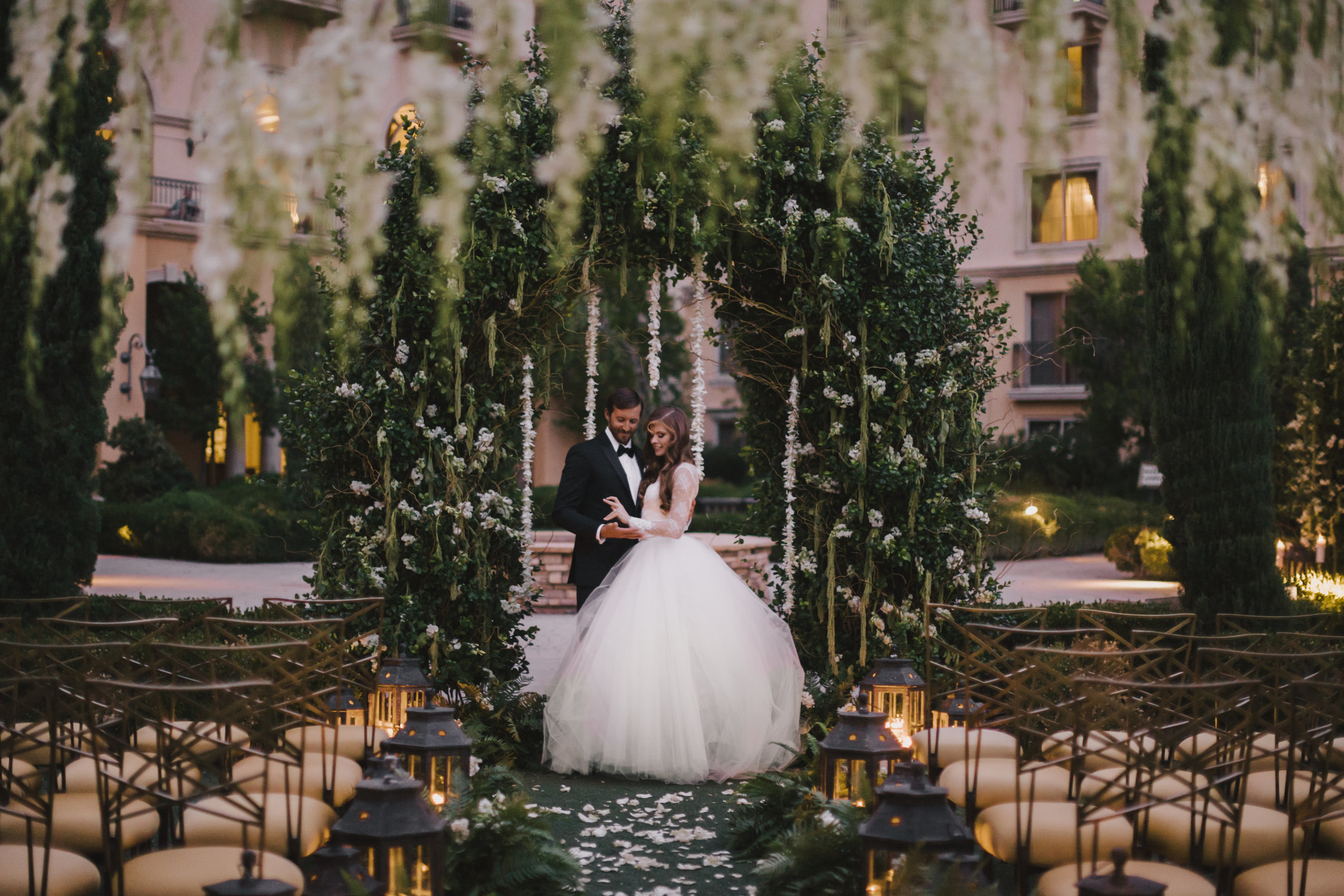 Couples wanting an enchanted forrest lean towards greenery and flowing white flowers in a beautiful outdoor wedding. Florals by Javier Valentino. Photo by Adam Trujillo.