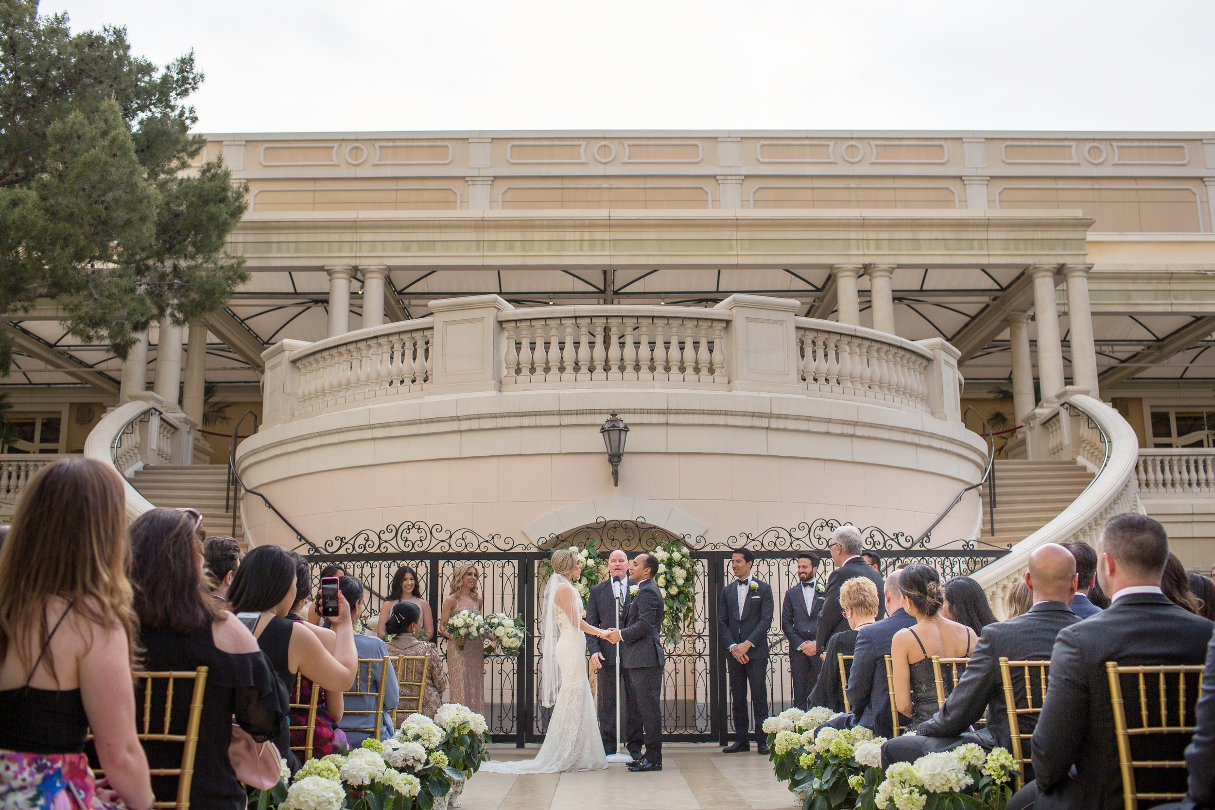 Outdoor wedding ceremony at Bellagio.Wedding Planner:  Andrea Eppolito Events   | Photography  D2 Tuscan Wedding Photography  | Videography  M Place Productions  | Venue & Catering:  Bellagio  | Floral & Decor:  Destinations by Design  | Lighting:  LED Unplugged   | Music: Classical Entertainment &  DJ Mike Fox  | Hair & Make Up:  Amelia C & Co