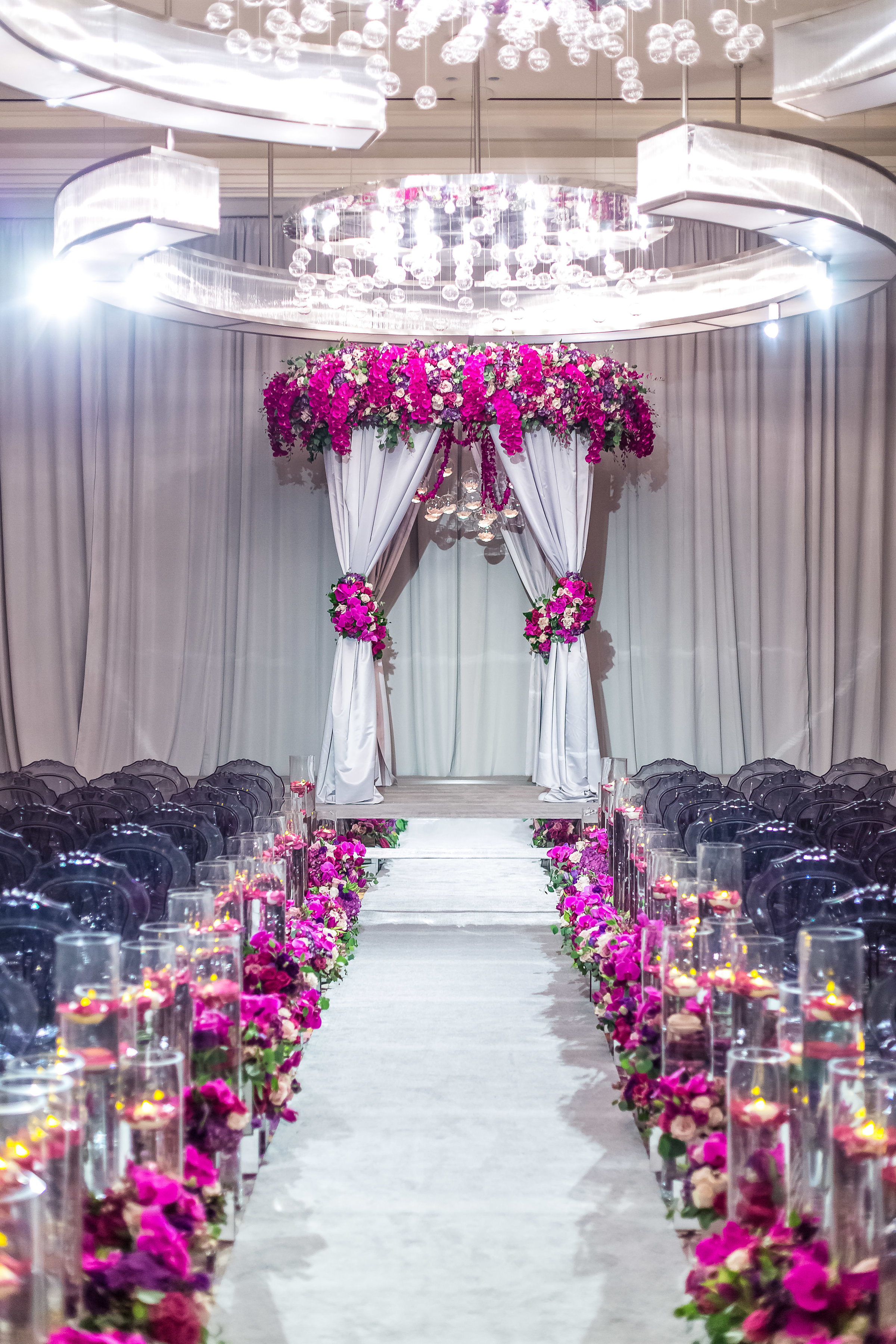Fuchsia orchids and grey drapes created a beautiful wedding ceremony in Las Vegas.  As seen in Inside Weddings.Wedding Planner: Andrea Eppolito Events    Photography  Brian Leahy    Videography  HOO Films    Venue & Catering:  Mandarin Oriental  / Waldorf Astoria   Floral & Decor: Destinations by Design    Lighting: LED Unplugged    Music:  DJ Breeze II    Hair & Make Up: Amelia C & Co