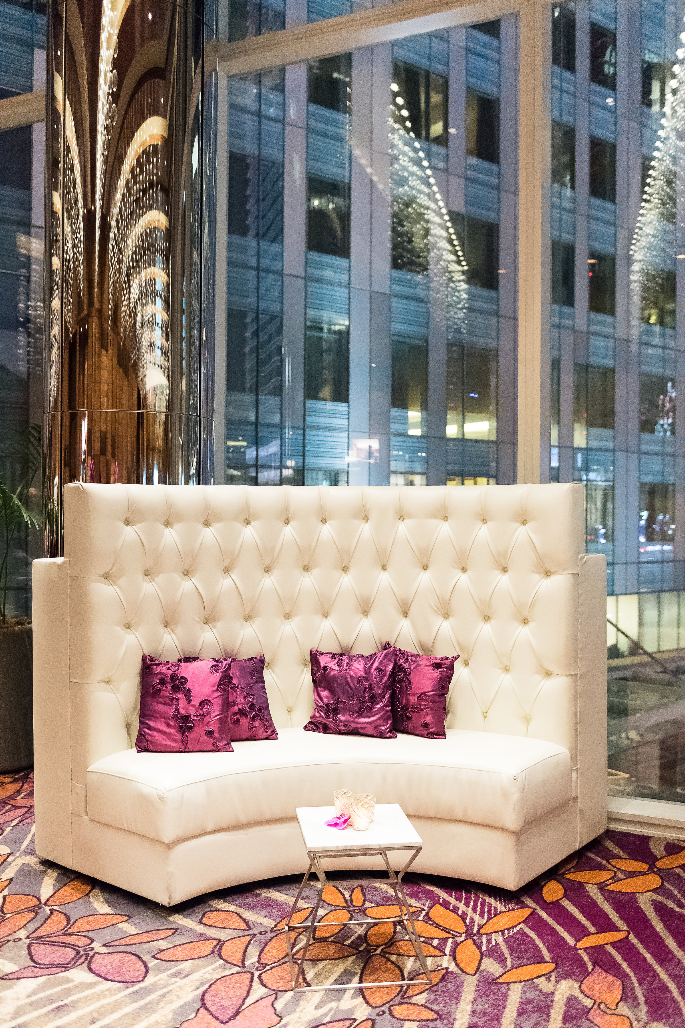 Tall white sofa at the cocktail reception of a wedding, Purple pillows.Wedding Planner: Andrea Eppolito Events    Photography  Brian Leahy    Videography  HOO Films    Venue & Catering: Mandarin Oriental / Waldorf Astoria   Floral & Decor: Destinations by Design    Lighting: LED Unplugged    Music: DJ Breeze II    Hair & Make Up: Amelia C & Co    Invitations by  Bliss & Bone    Menu and Escort Cards by  Meldeen