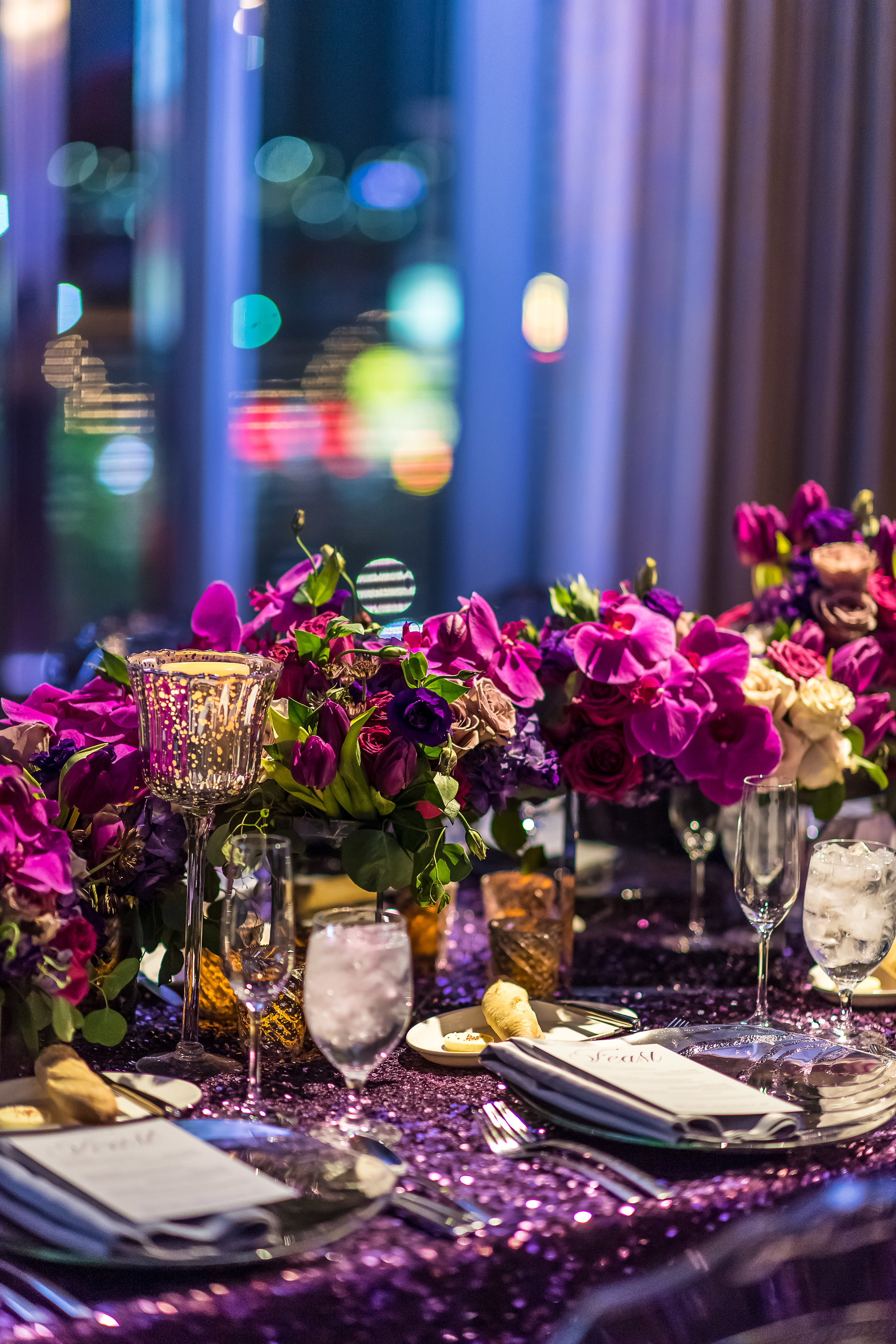 Long tables with low centerpieces with purple and pink flowers.Wedding Planner: Andrea Eppolito Events    Photography  Brian Leahy    Videography  HOO Films    Venue & Catering: Mandarin Oriental / Waldorf Astoria   Floral & Decor: Destinations by Design    Lighting: LED Unplugged    Music: DJ Breeze II    Hair & Make Up: Amelia C & Co    Invitations by  Bliss & Bone    Menu and Escort Cards by  Meldeen