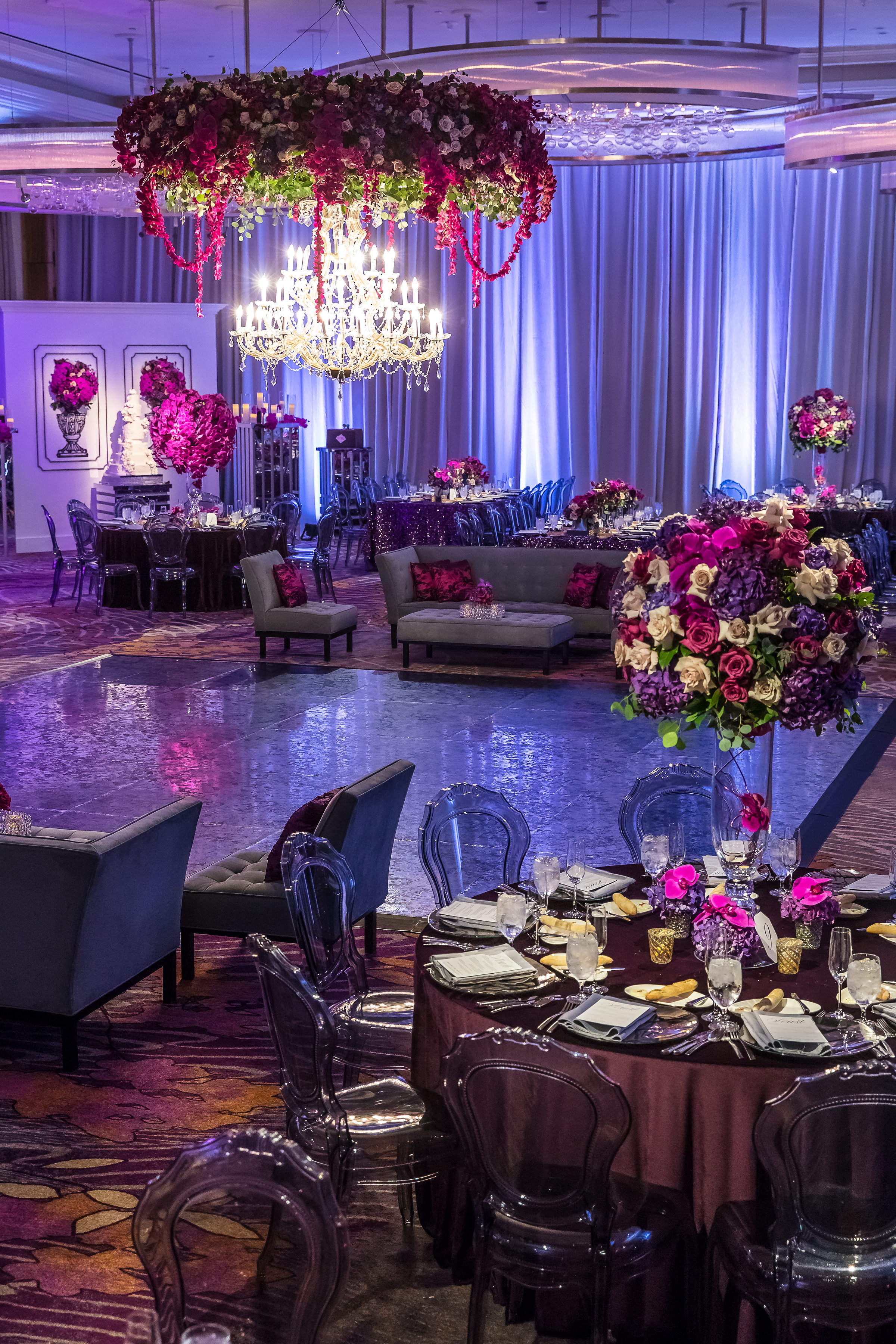 Massive Hanging Chandelier over a sweetheart table with orchid trees.Wedding Planner: Andrea Eppolito Events    Photography  Brian Leahy    Videography  HOO Films    Venue & Catering:  Mandarin Oriental  / Waldorf Astoria   Floral & Decor: Destinations by Design    Lighting: LED Unplugged    Music:  DJ Breeze II    Hair & Make Up: Amelia C & Co    Invitations by  Bliss & Bone    Menu and Escort Cards by  Meldeen