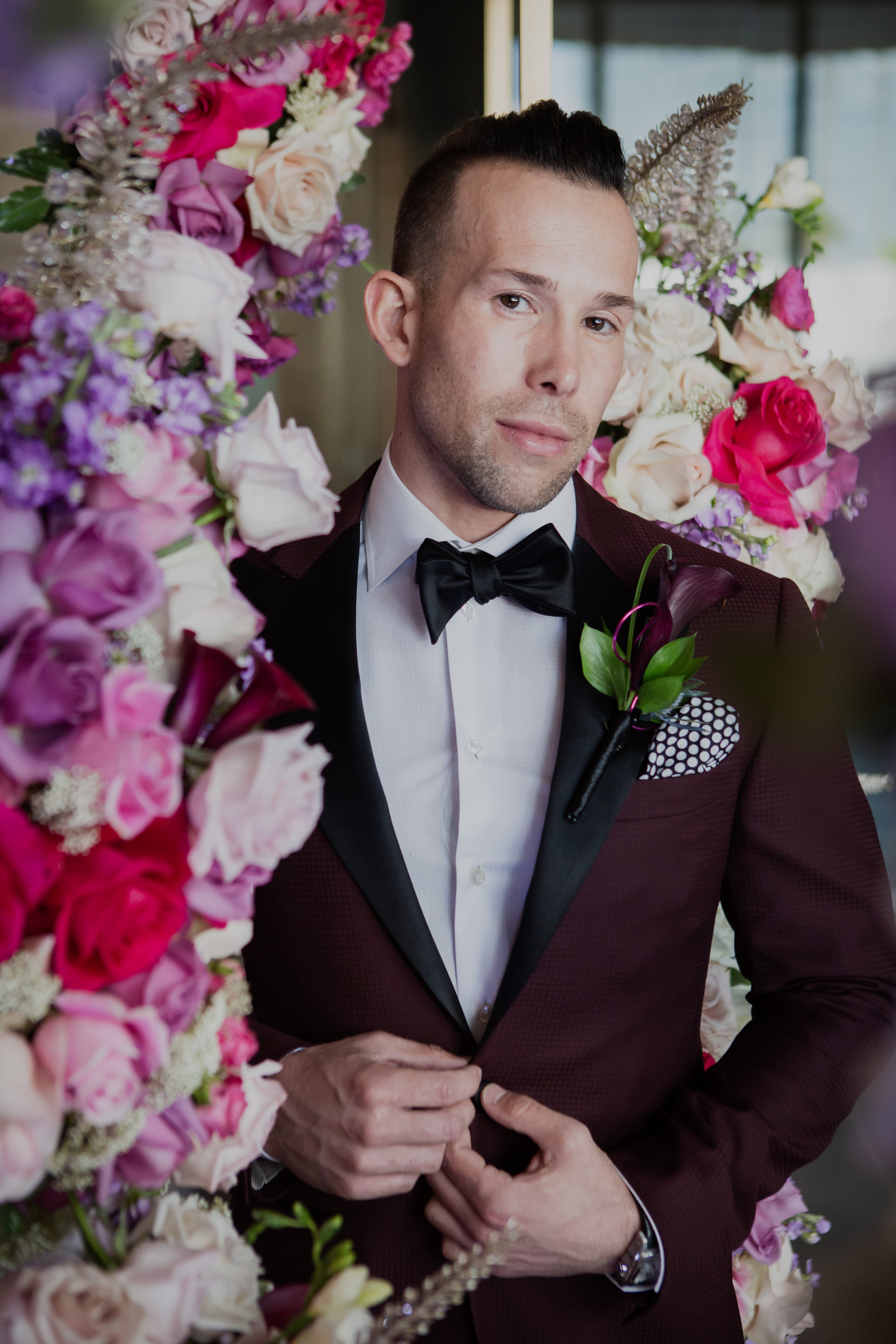 Groom in custom maroon tuxedo by Stitched. Las Vegas Wedding Planner & Event Designer  Andrea Eppolito Events  · Photography by  Adam Frazier Photo  · Video by  M Place Productions  · Floral & Decor by  DBD Las Vegas  · Venue  ARIA Primrose Ballroom  · Cigar Band by  Royal Cigar Company  and  Jason of Beverly Hills  · Beauty by  Glammed Up Las Vegas  · Dress by  Vera Wang  · Salon  Couture Bride Las Vegas  · Shoes  Bella Belle Shoes  · Bride  Katrina May Armenta  · Groom  Lucas Cuevas